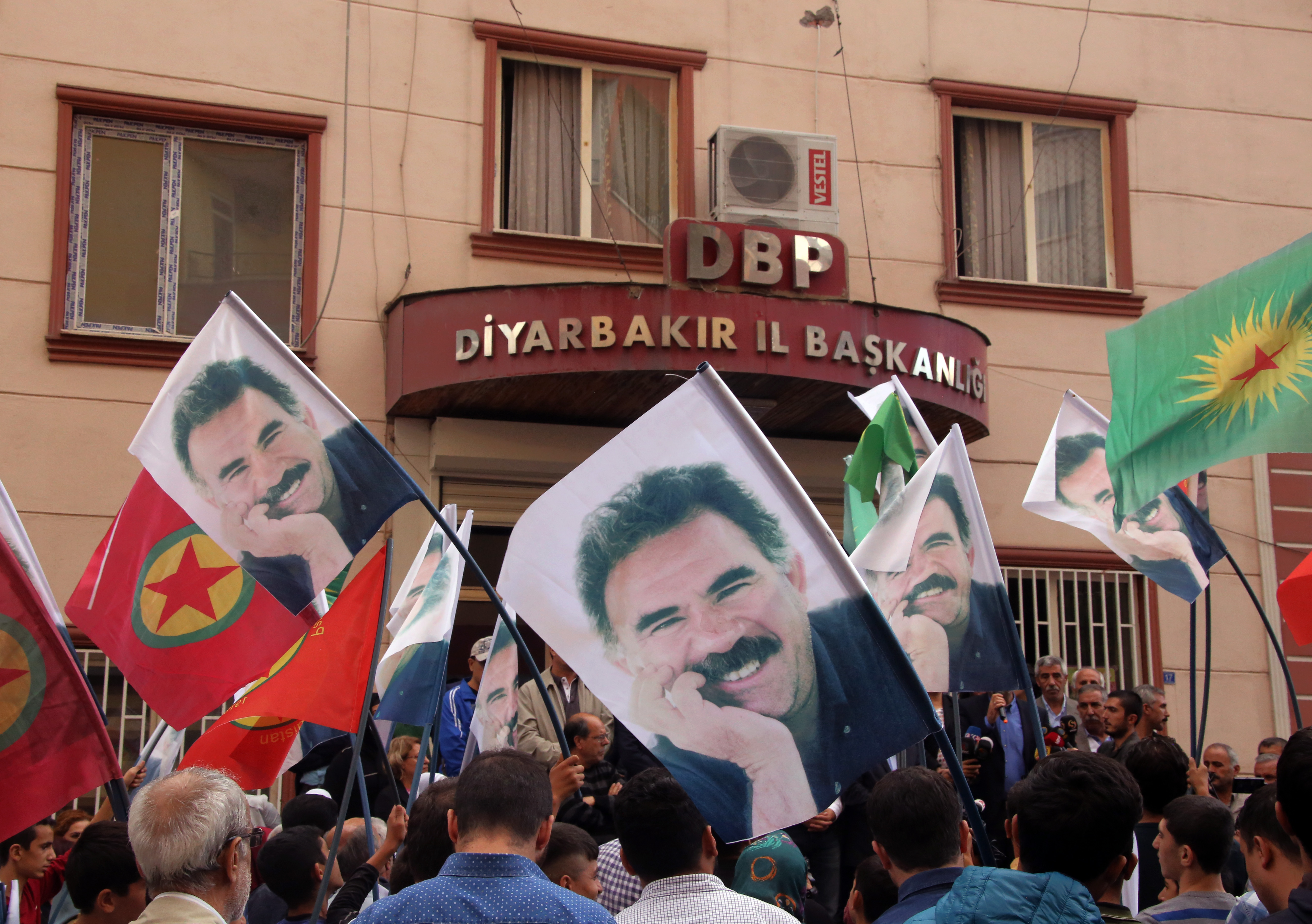 People hold posters of jailed PKK leader Abdullah Ocalan and PKK flags as they gather outside the headquarters of pro-Kurdish Democratic Regions Party, DBP, on the17th anniversary of Ocalan's expulsion from Syria, in Diyarbakir, Turkey, Oct. 9, 201...