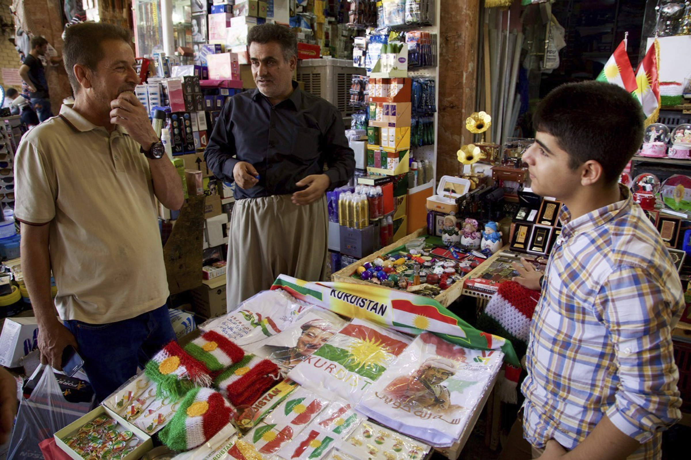 FILE - A salesman, talking to a customer, sells patriotic and pro-independence paraphanelia at a bazaar in Irbil, Iraq, Aug. 24, 2017.