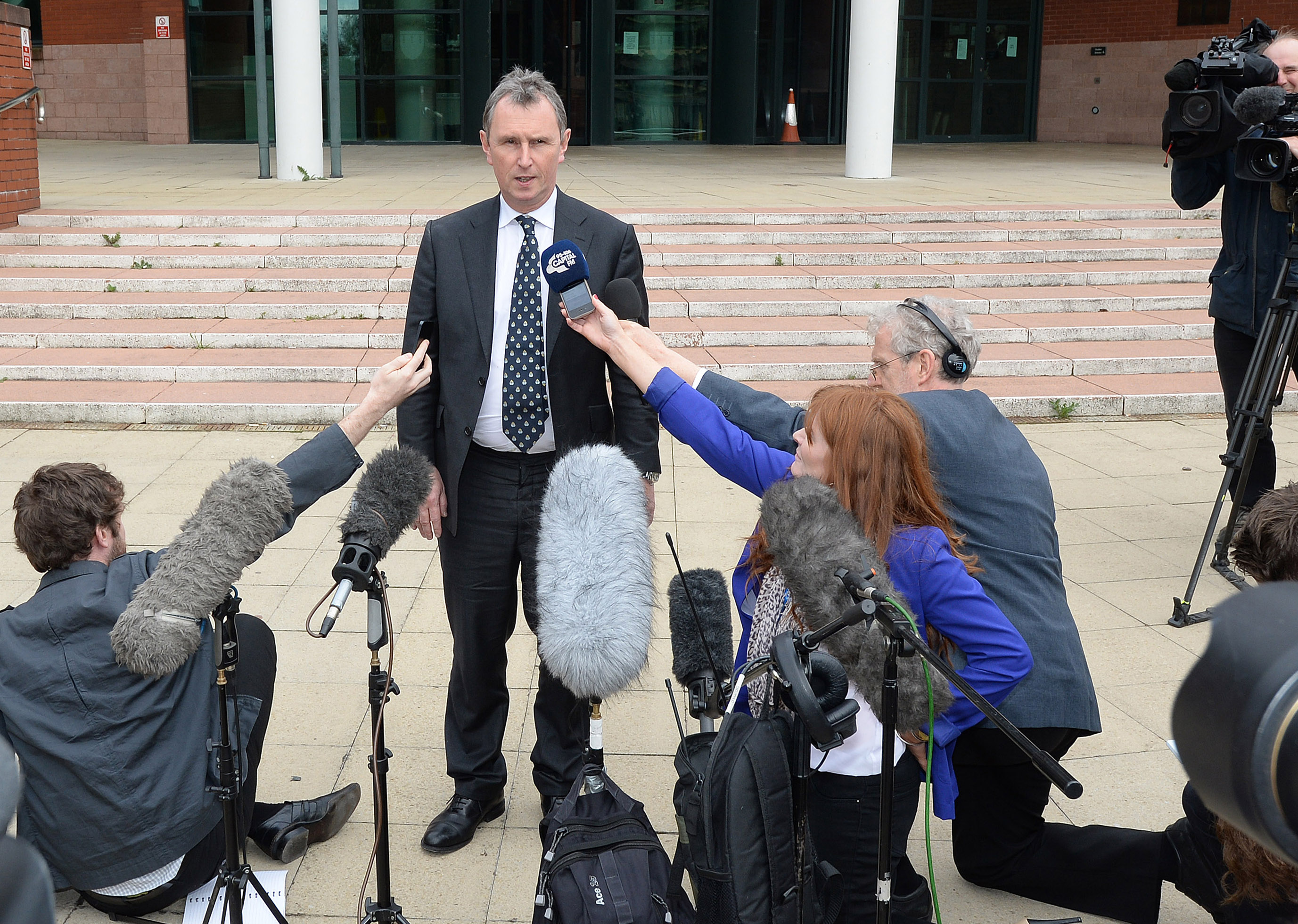 FILE - Former deputy speaker of the House of Commons Nigel Evans speaks to the media, after the end of his trial, outside Preston Crown Court, northern England, Apr. 10, 2014