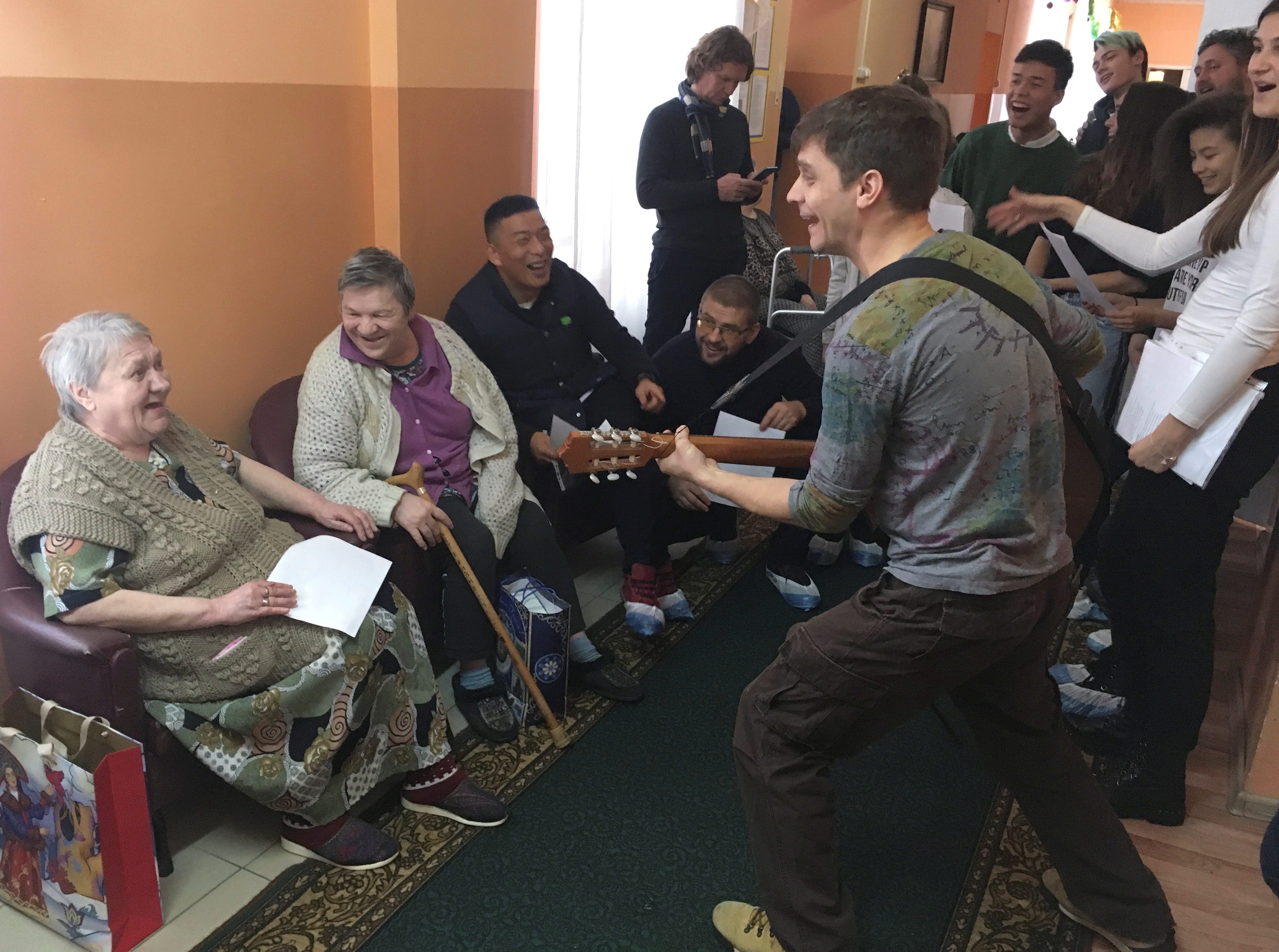 """Volunteers entertain women at a nursing home, as part of the """"Aging with Joy"""" charity project, in the settlement of Khatun in Moscow Region, Dec. 13, 2018."""