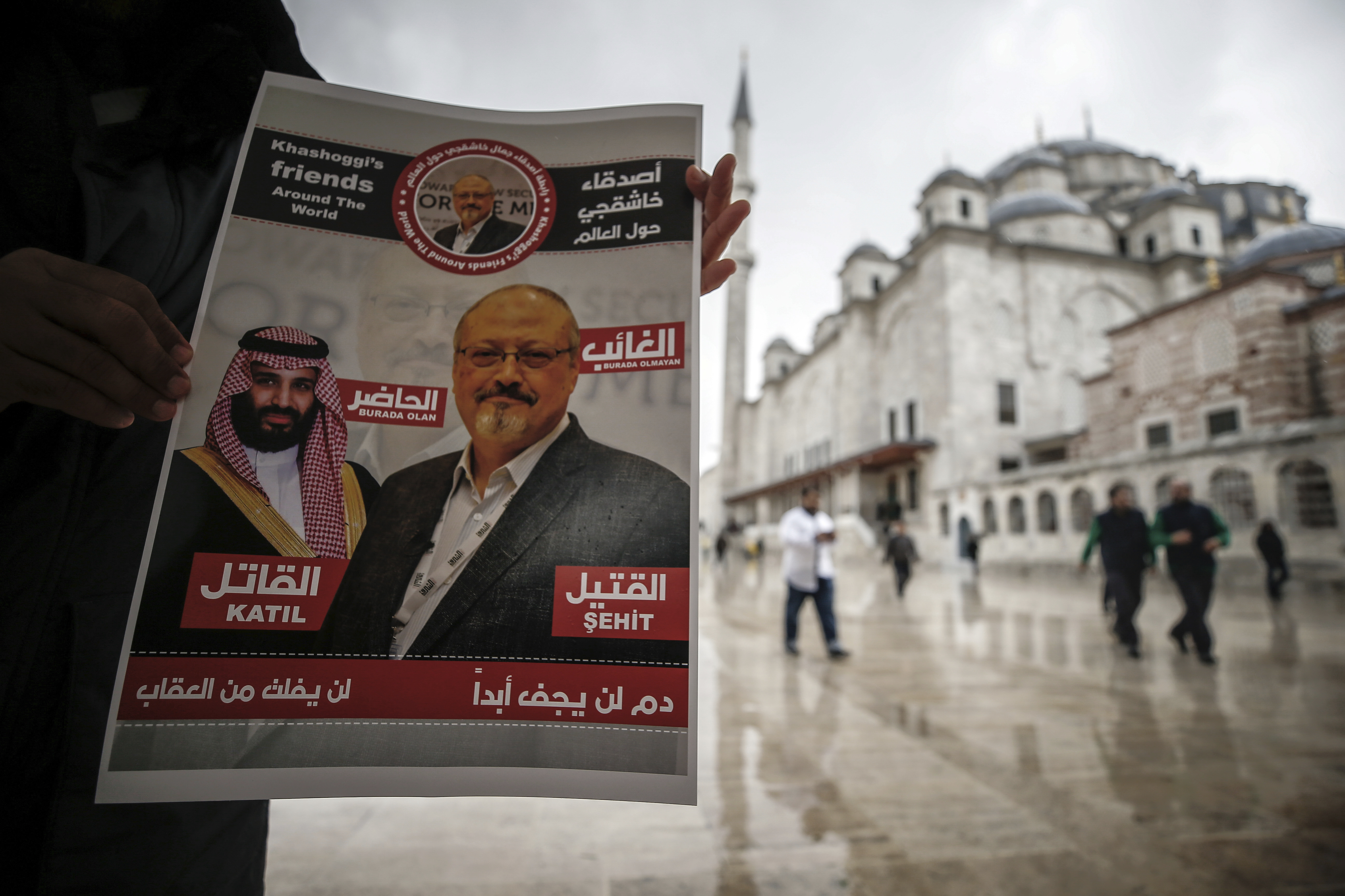 "A man holds a poster showing images of Saudi Crown Prince Muhammed bin Salman and of journalist writer Jamal Khashoggi, describing the prince as ""assassin"" and Khashoggi as ""martyr"" during funeral prayers in absentia for Khashoggi who was killed last"