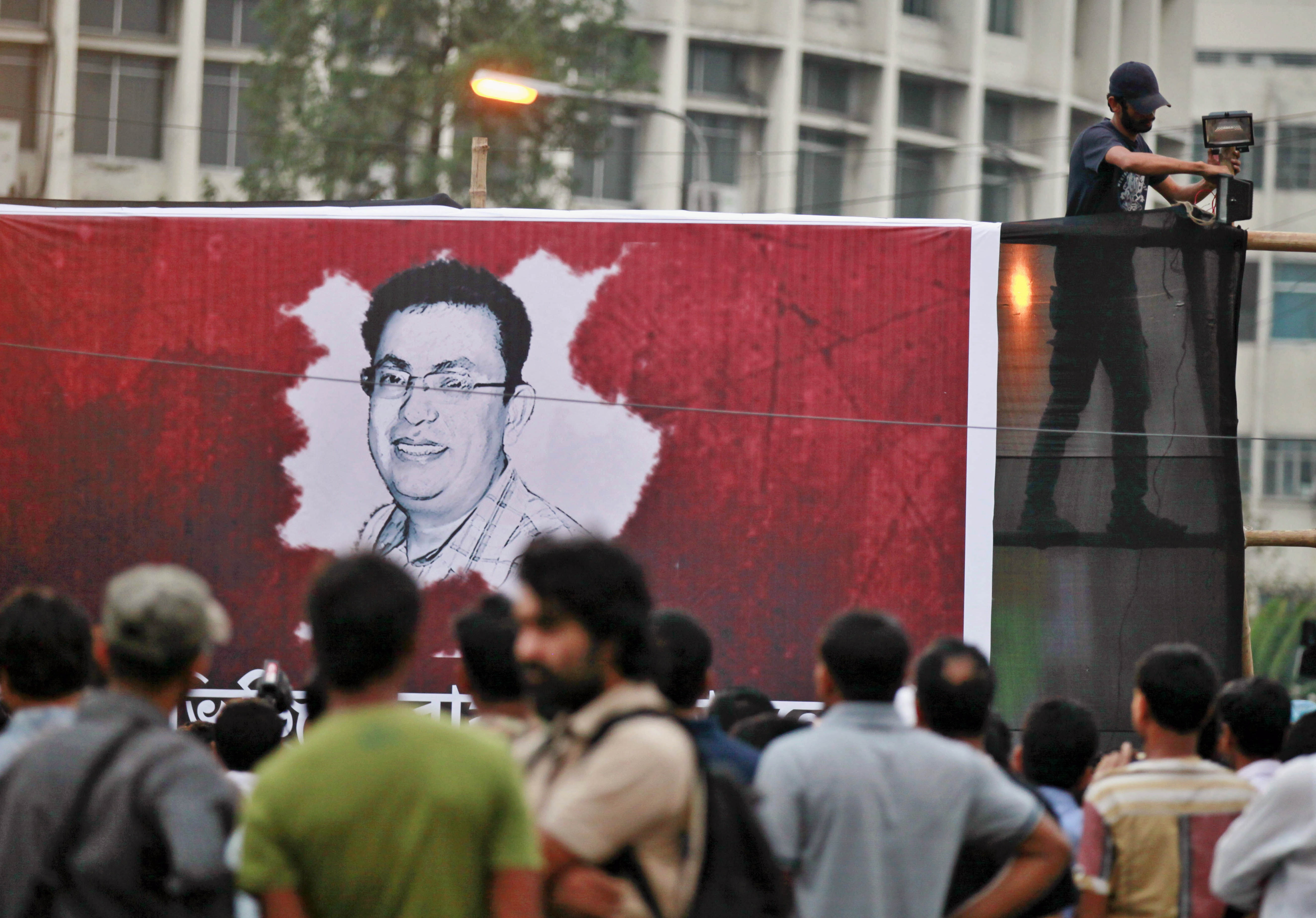 FILE - A Bangladeshi activist sets up a light on a poster displaying a portrait of slain Bangladeshi-American blogger Avijit Roy in Dhaka, Bangladesh, Feb. 27, 2015.
