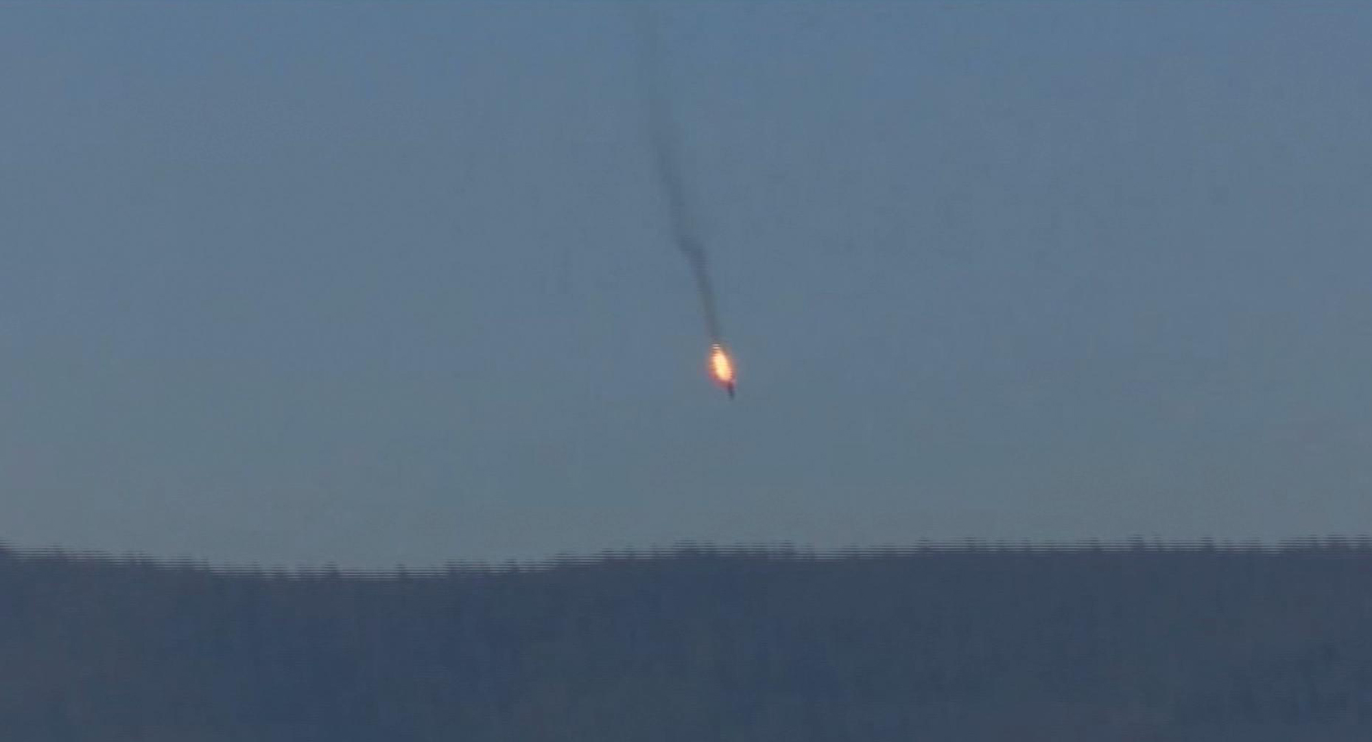 This frame grab from video by Haberturk TV, shows a Russian warplane on fire before crashing on a hill as seen from Hatay province, Turkey, Nov. 24, 2015.