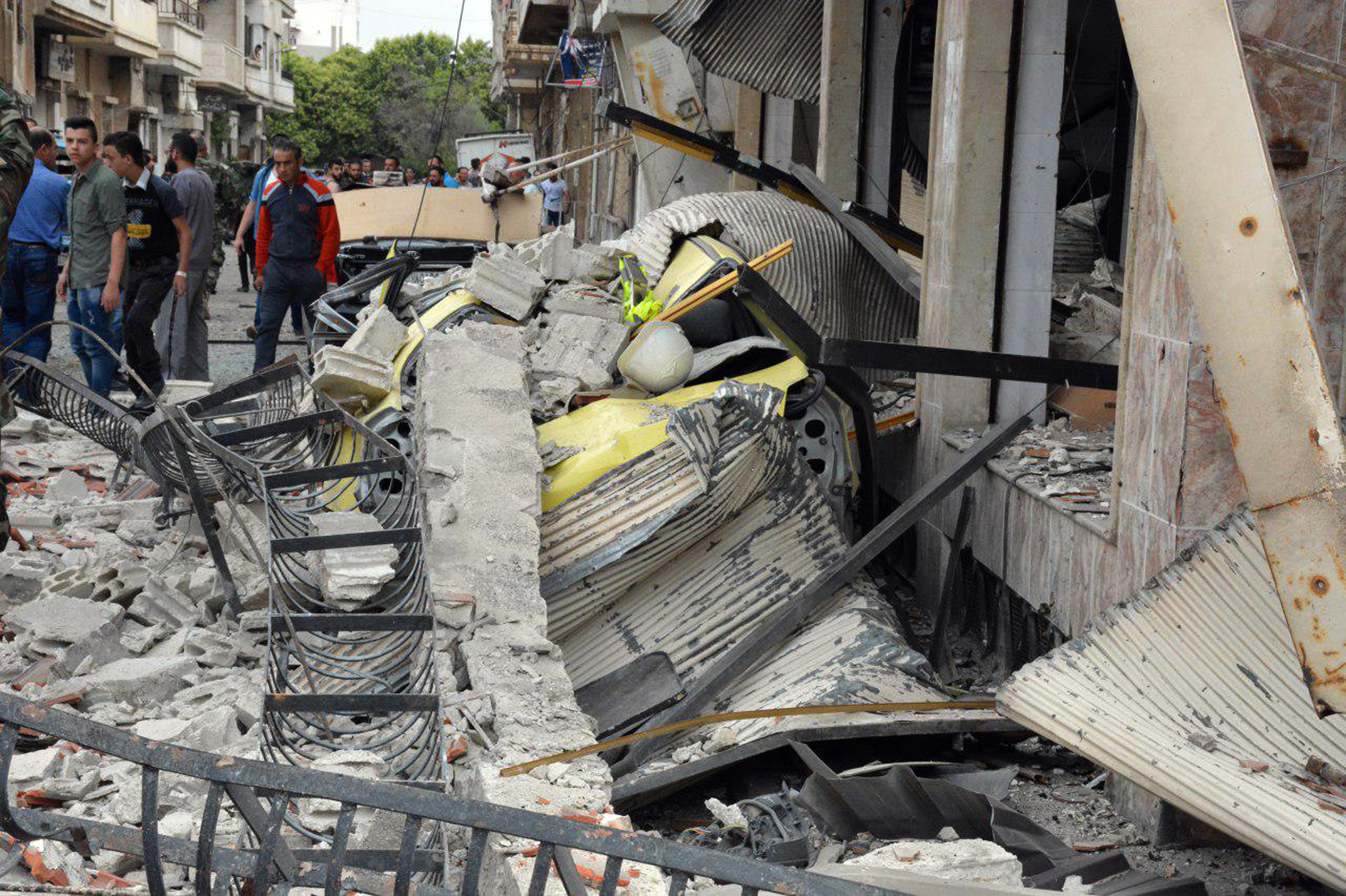 In this photo released by the Syrian official news agency SANA, Syrian citizens gather at the scene of an explosion in the central city of Homs, Syria.
