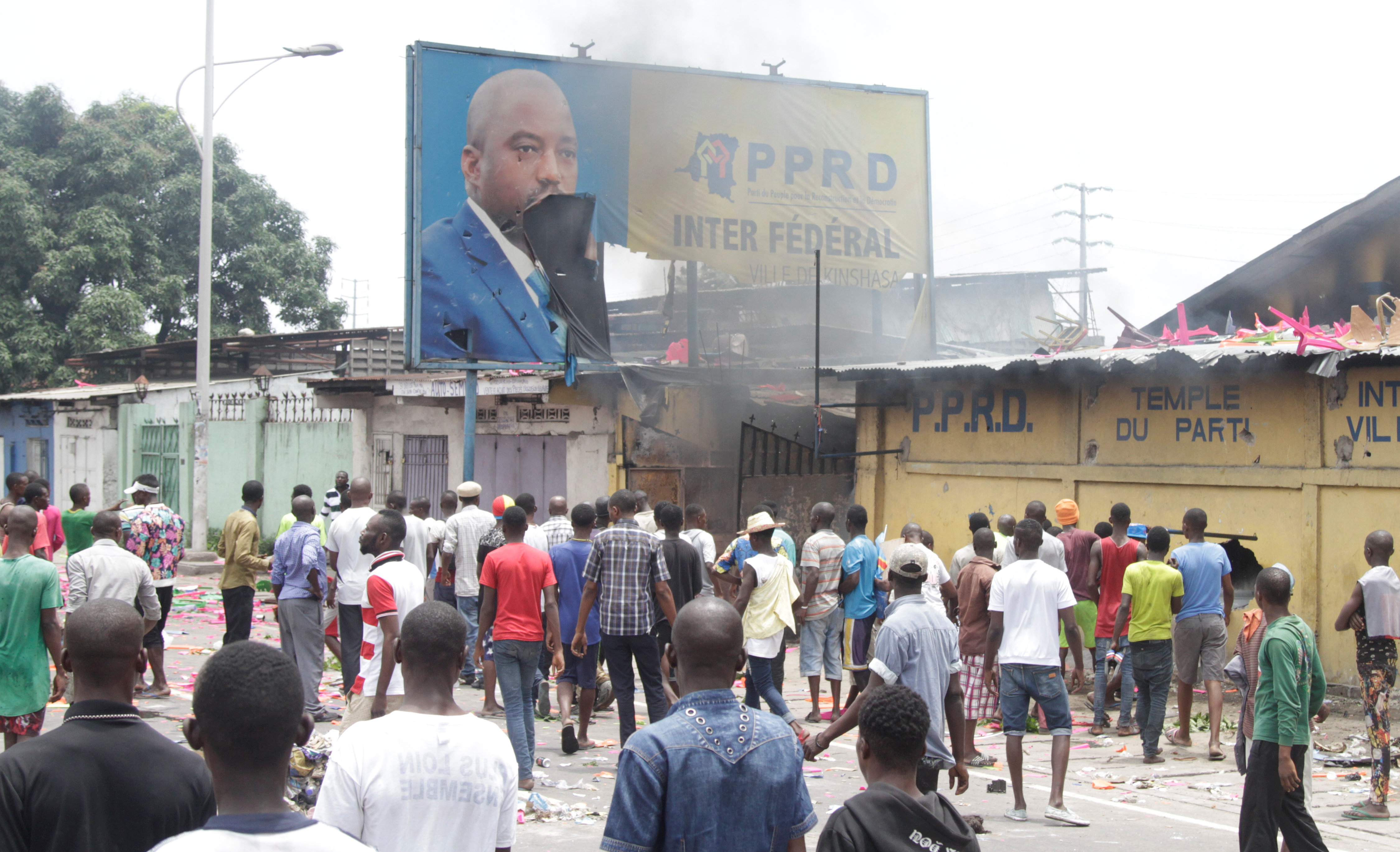 FILE - Congolese opposition supporters chant slogans as they destroy the billboard of President Joseph Kabila during a march to press the President to step down in the Democratic Republic of Congo's capital Kinshasa, Sept. 19, 2016.