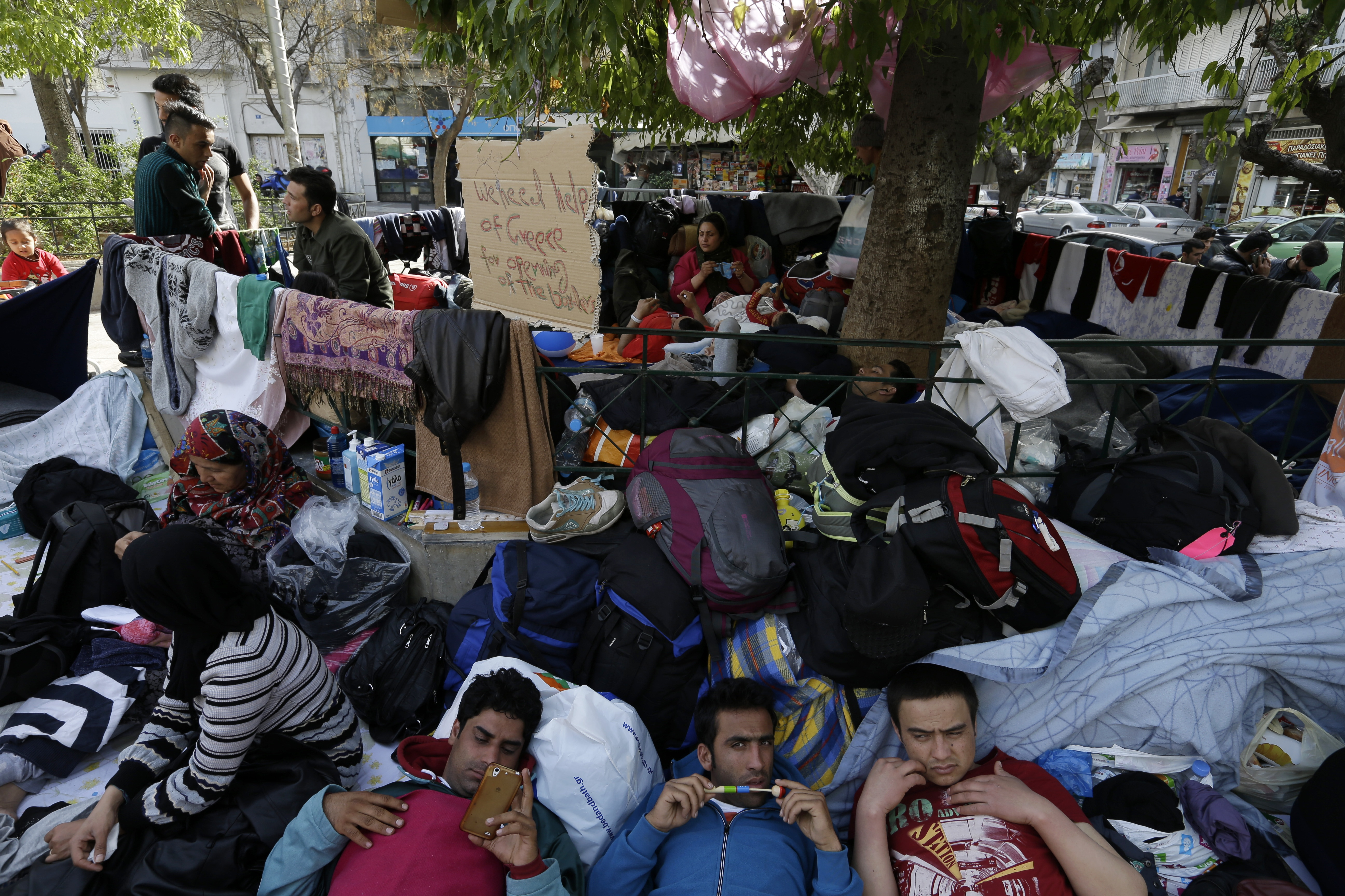 Migrants rest under a tree at the Victoria Square in Athens, Greece, March 1, 2016.