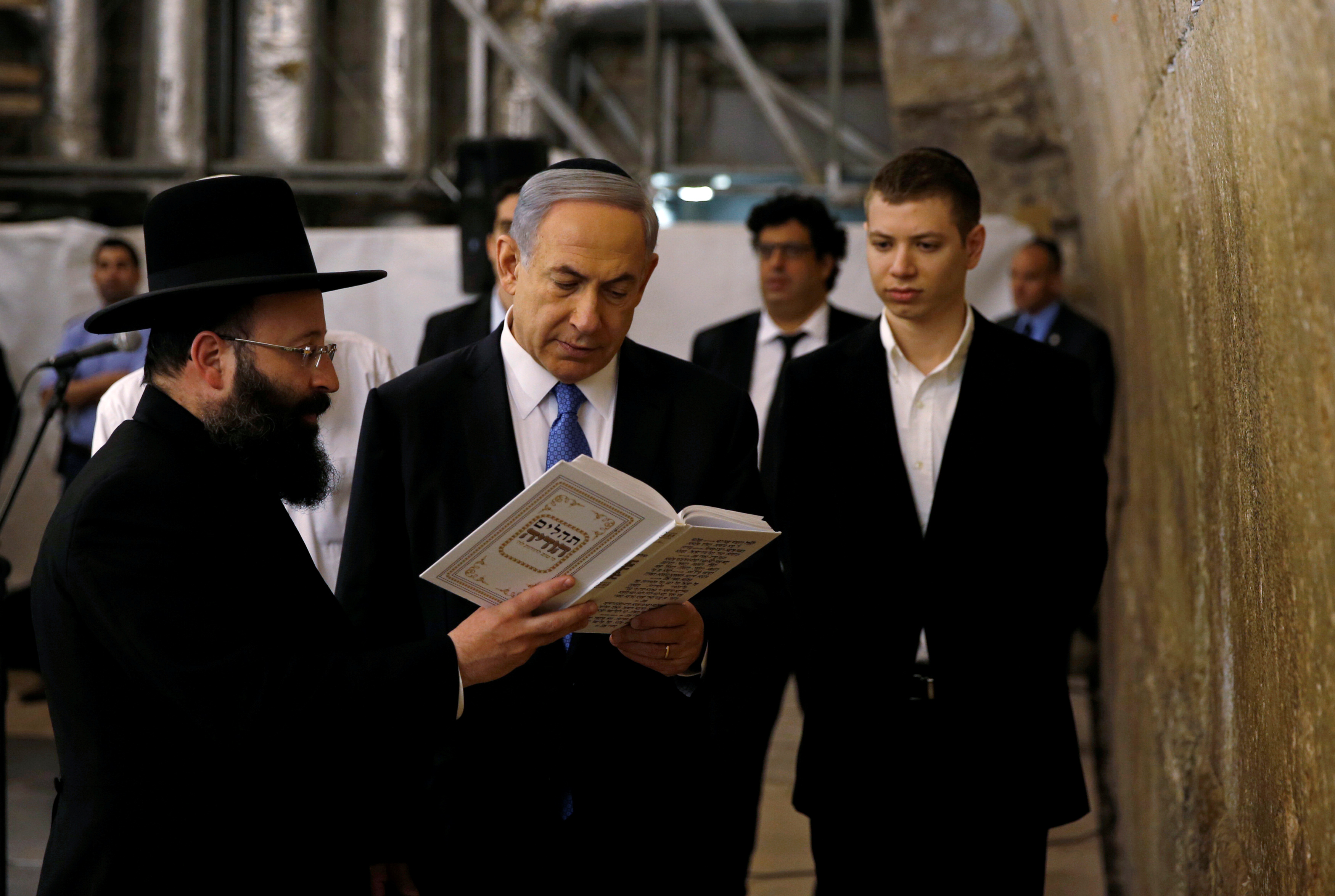 FILE PHOTO: Israel's Prime Minister Benjamin Netanyahu (C) reads a prayer with Western Wall Rabbi Shmuel Rabinowitz (L) as his son Yair (R) stands next to him, at the Western Wall, Judaism's holiest prayer site, in Jerusalem's Old City March 18, 2015...