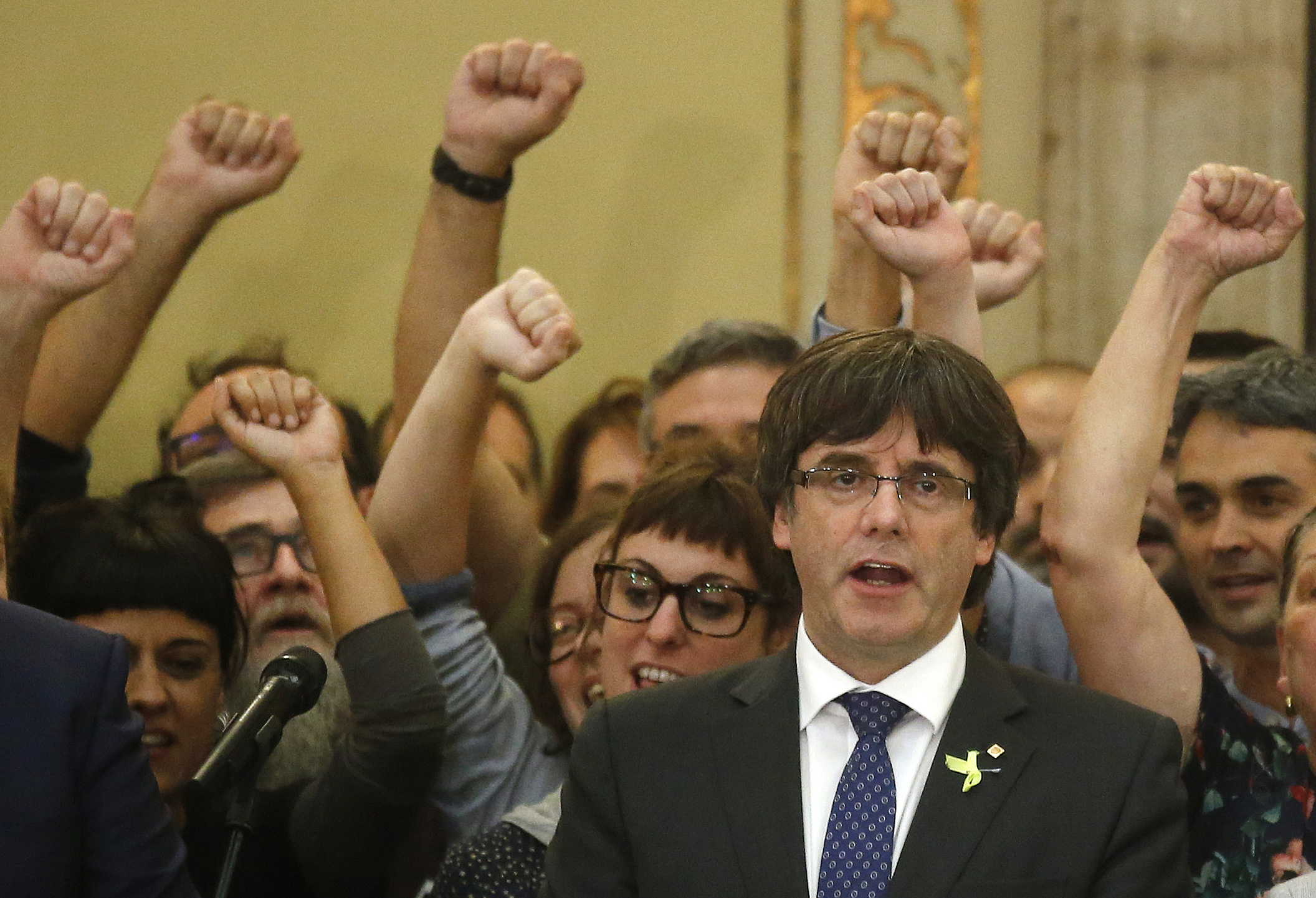 Catalan President Carles Puigdemont sings the Catalan anthem inside the parliament after a vote on independence in Barcelona, Spain, Oct. 27, 2017.