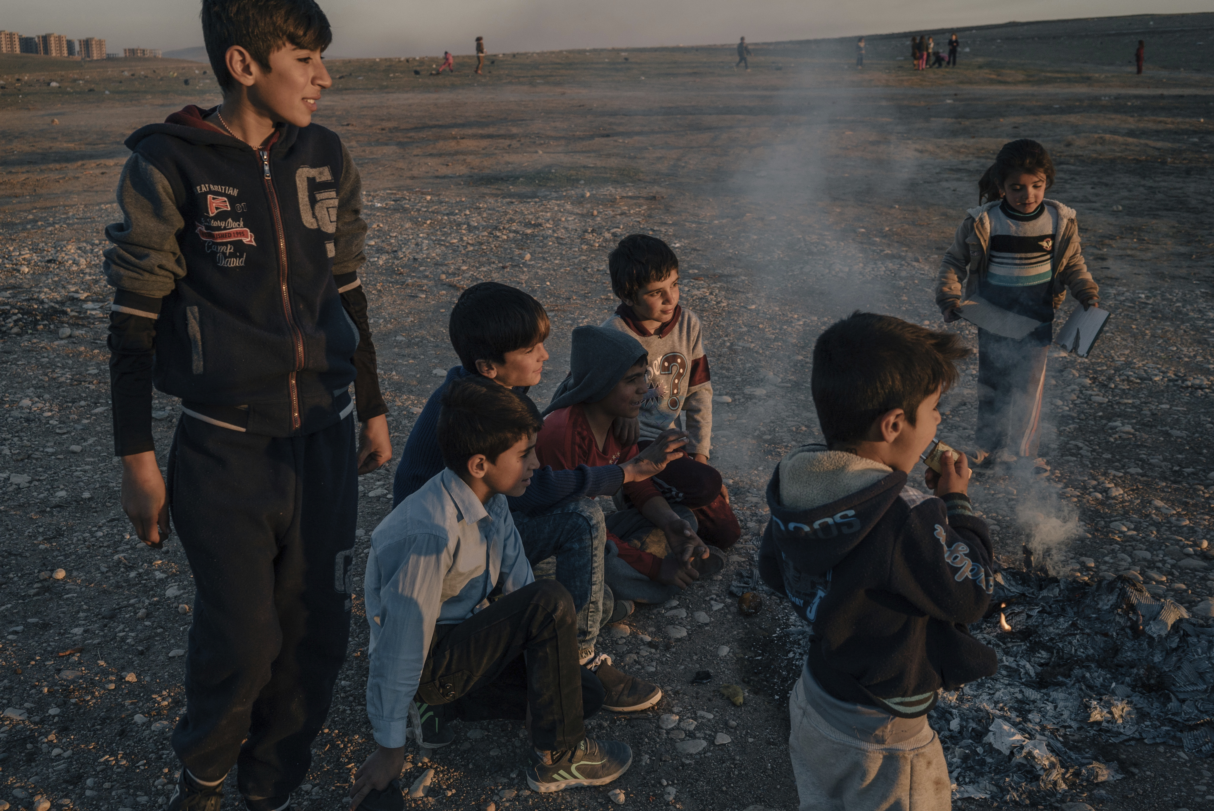 Yazidi children play at sunset outside the Kabarto camp for civilians displaced by war in Iraq, Jan. 11, 2017.
