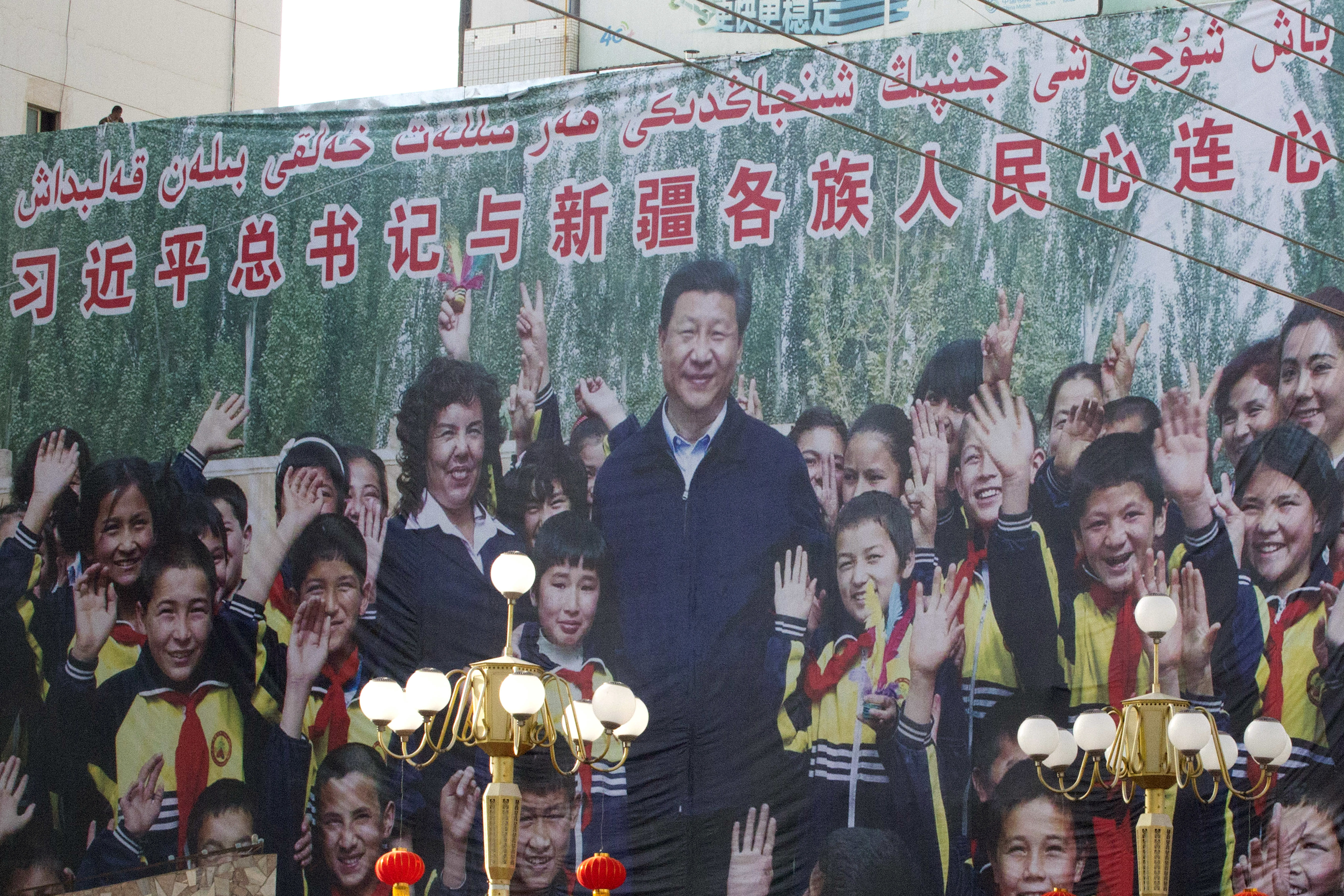 """FILE - A propaganda poster showing Chinese President Xi Jinping with ethnic minority children and the slogan which reads """"Party Secretary Xi Jinping and Xinjiang's multi ethnic residents united heart to heart"""" decorates the side of a building in Kash"""