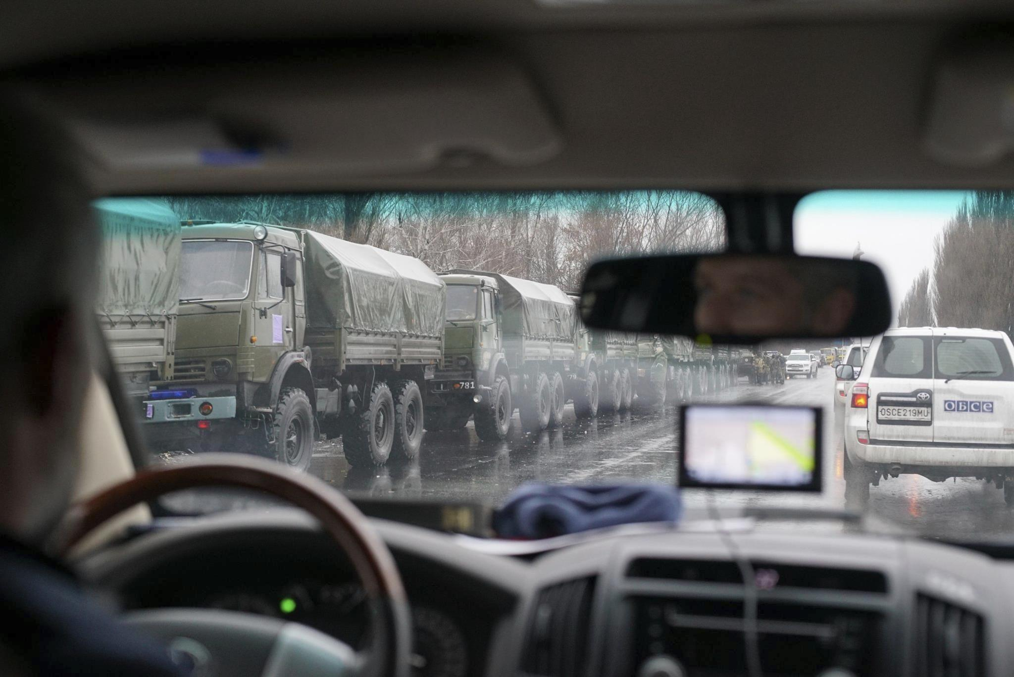 In this OSCE monitoring mission photo taken Nov. 21, 2017, in Ukraine's eastern city of Luhansk, armored personnel carriers and armed men drive in the city center. Dozens of armed people in combat fatigues deployed Nov. 22 to main administrative buil...