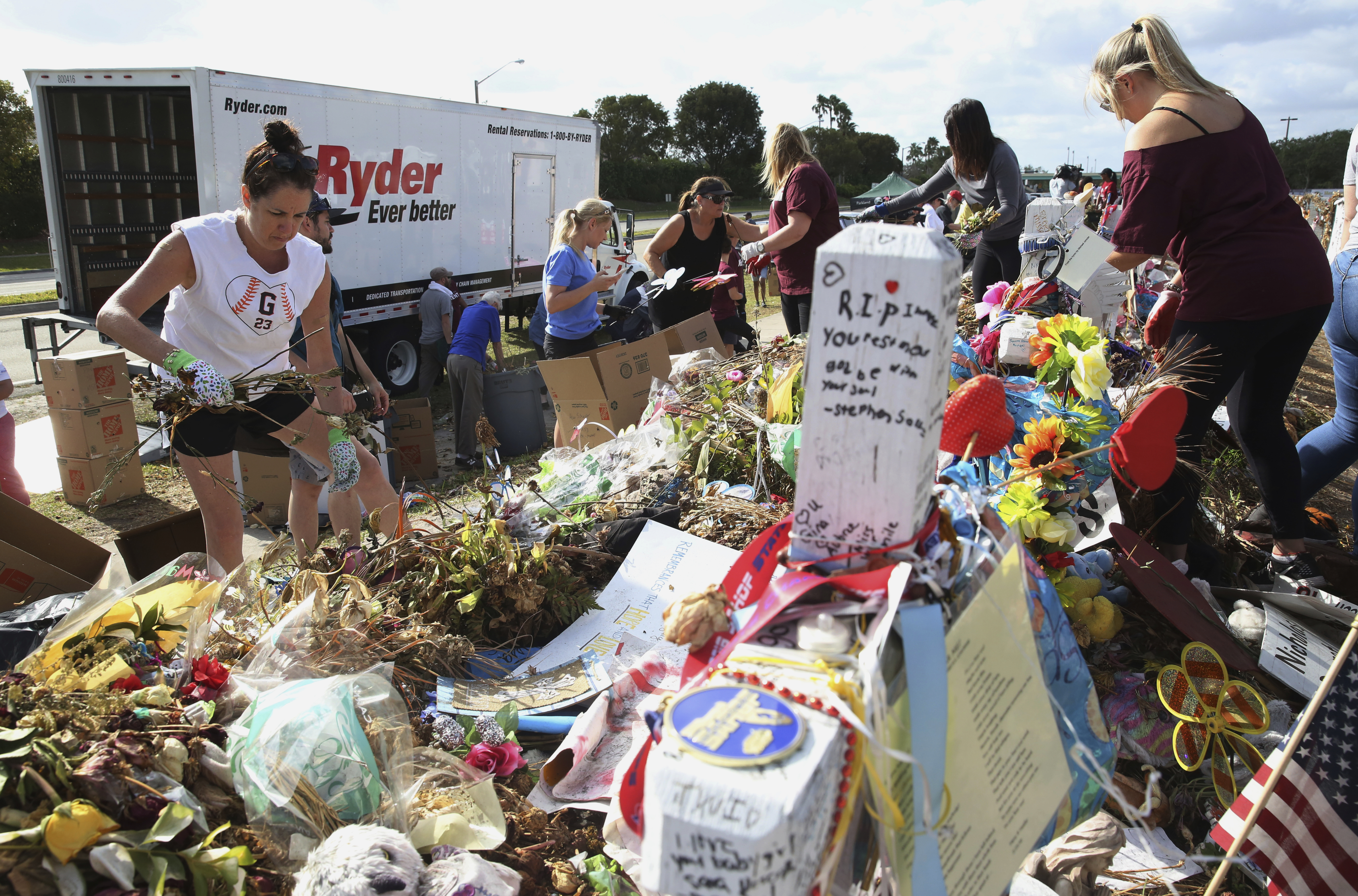Volunteers, students and parents sort items left at the memorial site for the 17 students and faculty killed at Marjory Stoneman Douglas High School, March 28, 2018 in Parkland, Florida. Flowers and plants will be composted while all other items will...