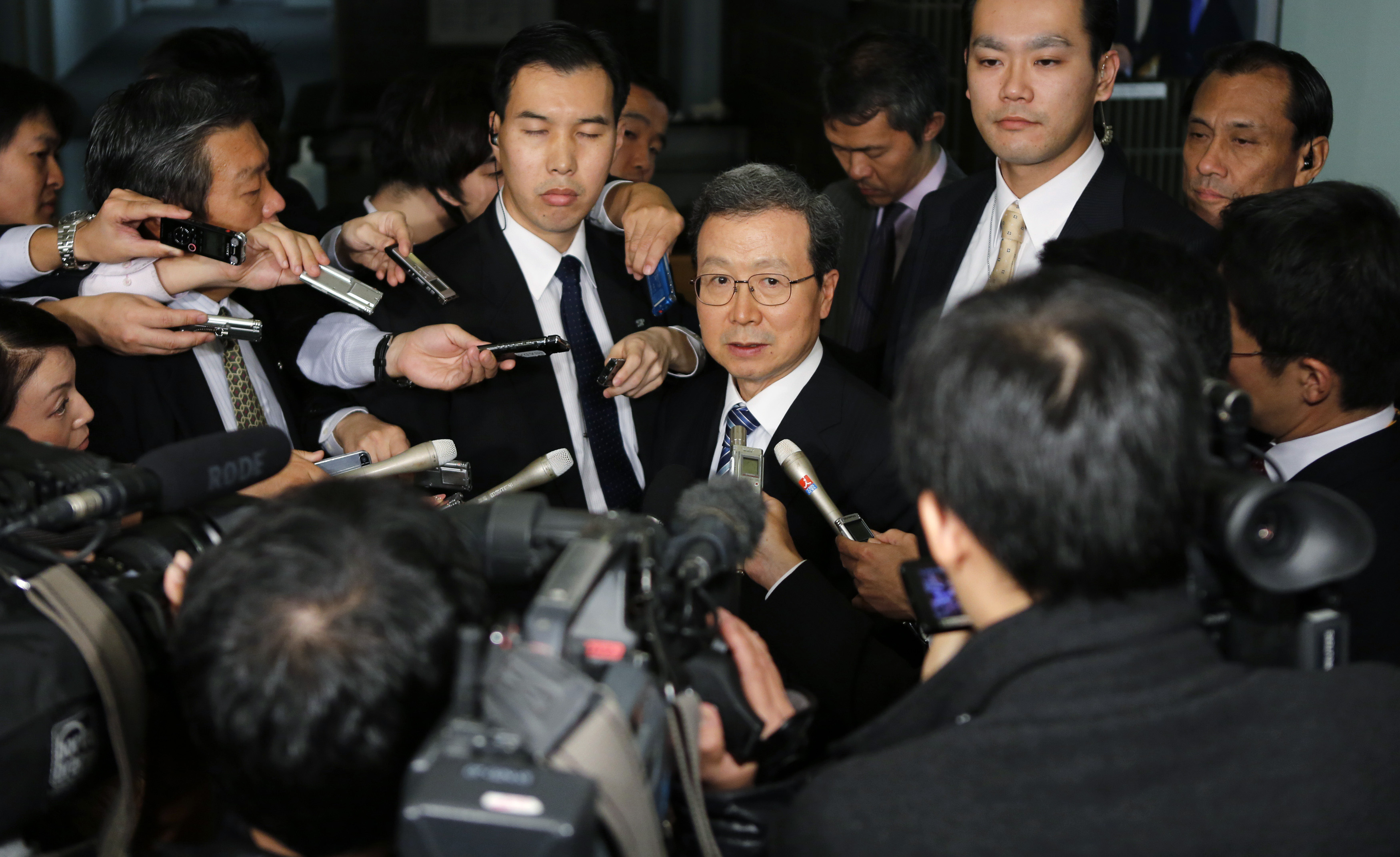 Cheng Yonghua, center, Chinese ambassador to Japan, is surrounded by the media as he speaks after meeting with Japan's Vice Minister for Foreign Affairs Akitaka Saiki at the Foreign Ministry in Tokyo, Nov. 25, 2013. Asian aviation officials said air...