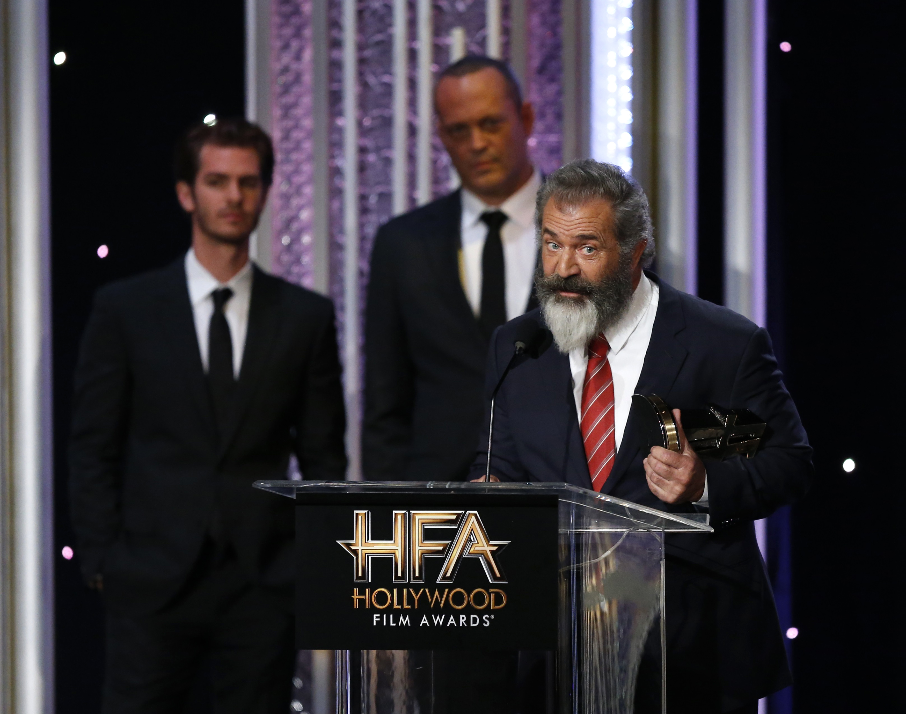 "Director Mel Gibson accepts the Hollywood Director Award for ""Hacksaw Ridge"" as cast members Andrew Garfield, left, and Vince Vaughn look on at the Hollywood Film Awards in Beverly Hills, Calif., Nov. 6, 2016."