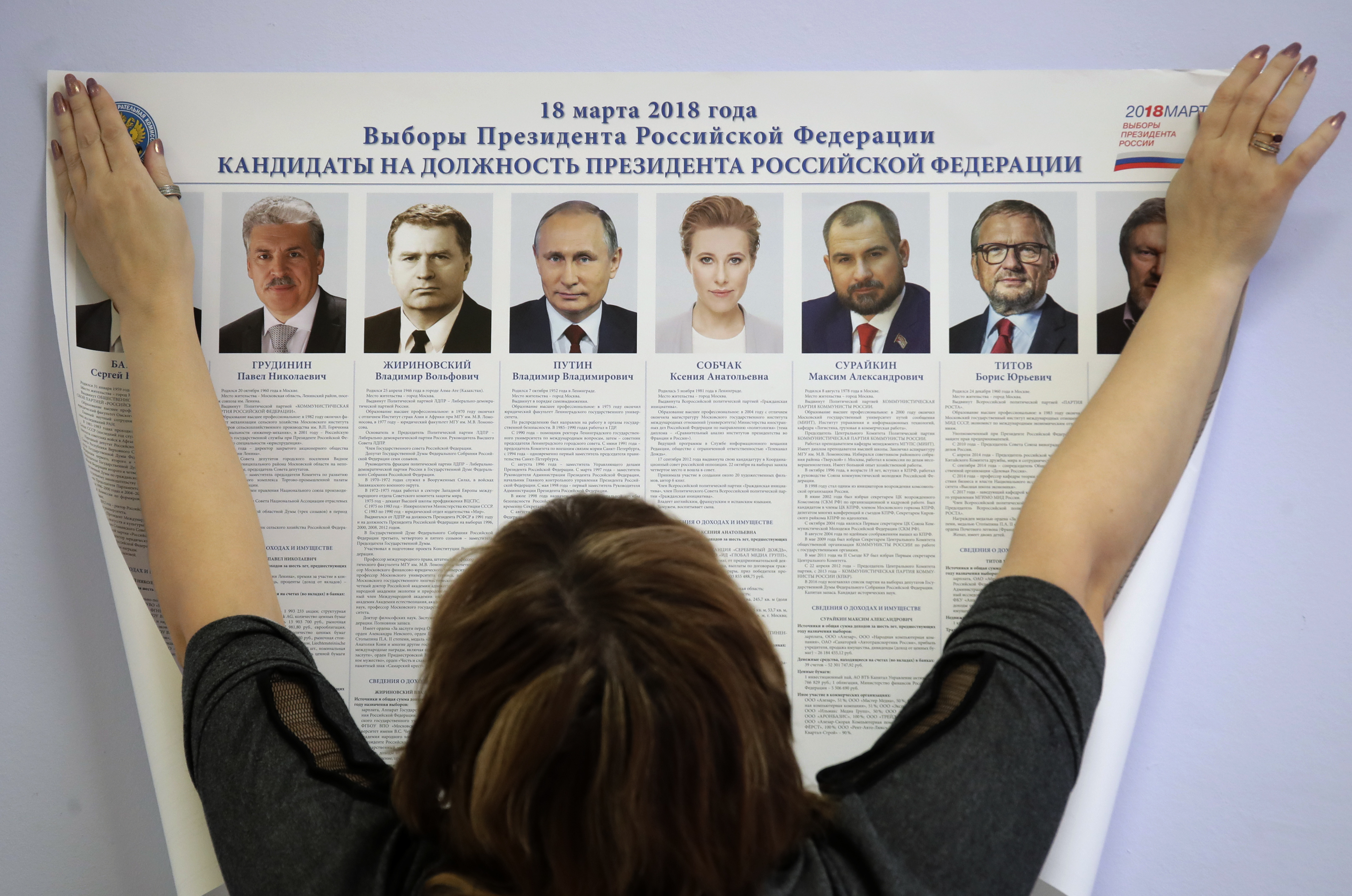A polling station employee hangs a list of candidates for the 2018 Russian presidential election during preparations for the election at a polling station in St.Petersburg, Russia, March 16, 2018. The presidential elections will be held in Russia Mar...