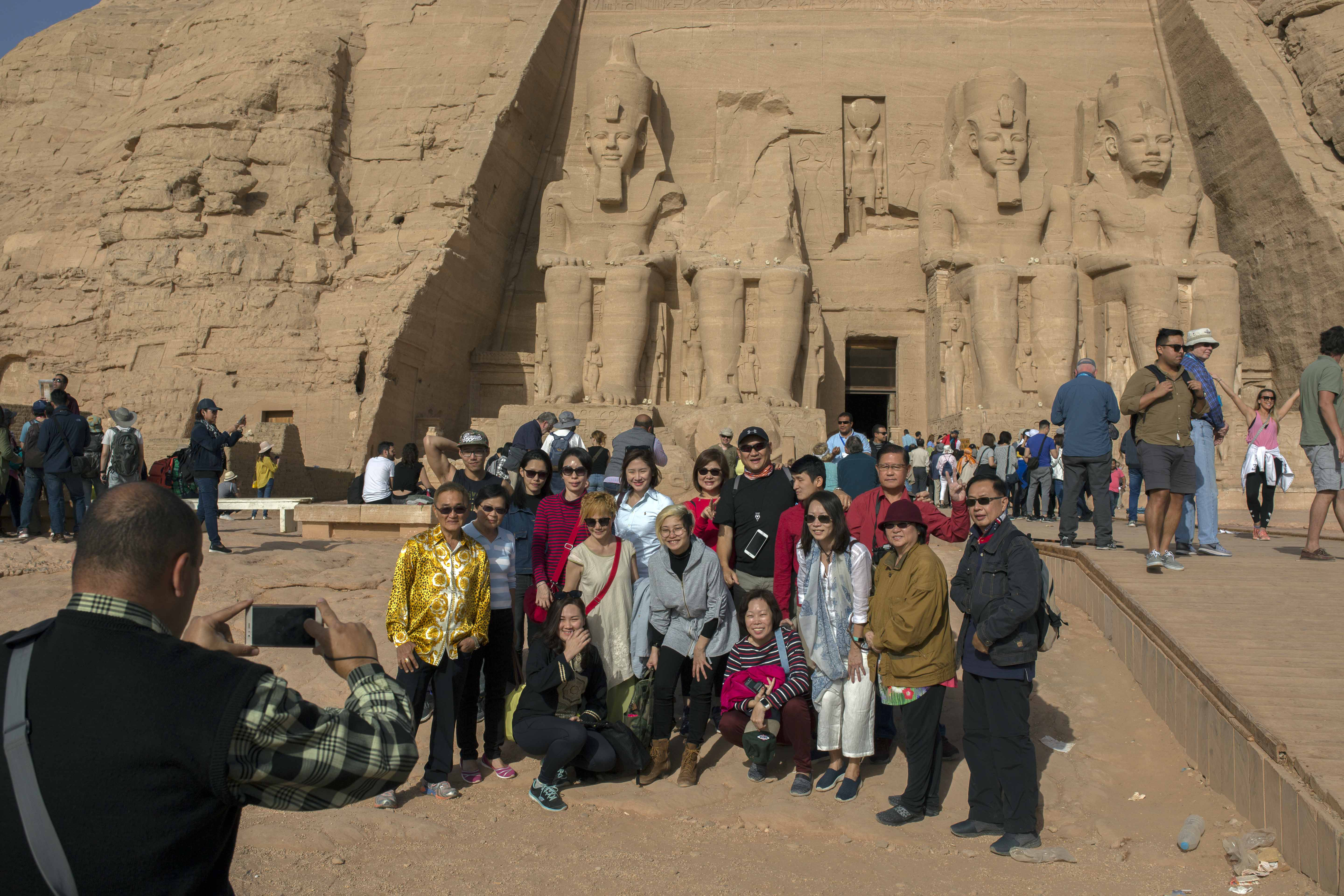 Tourists pose for a group portrait at Abu Simbel temple in Aswan, southern Egypt, after the rituals of the sun festival ended Thursday, Feb. 22, 2018. (H. Elrasam/VOA)