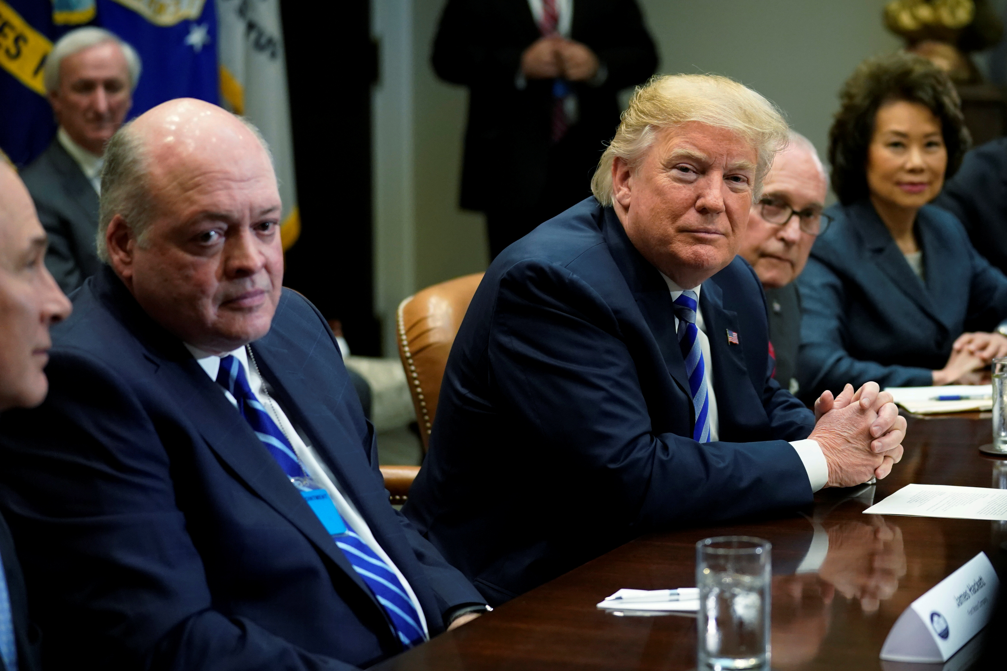 U.S. President Donald Trump, flanked by Ford CEO James Hackett, left, and White House chief economic adviser Larry Kudlow, 2nd right, and Transportation Secretary Elaine Chao, meets with chief executives of major U.S. and foreign automakers at the Wh...