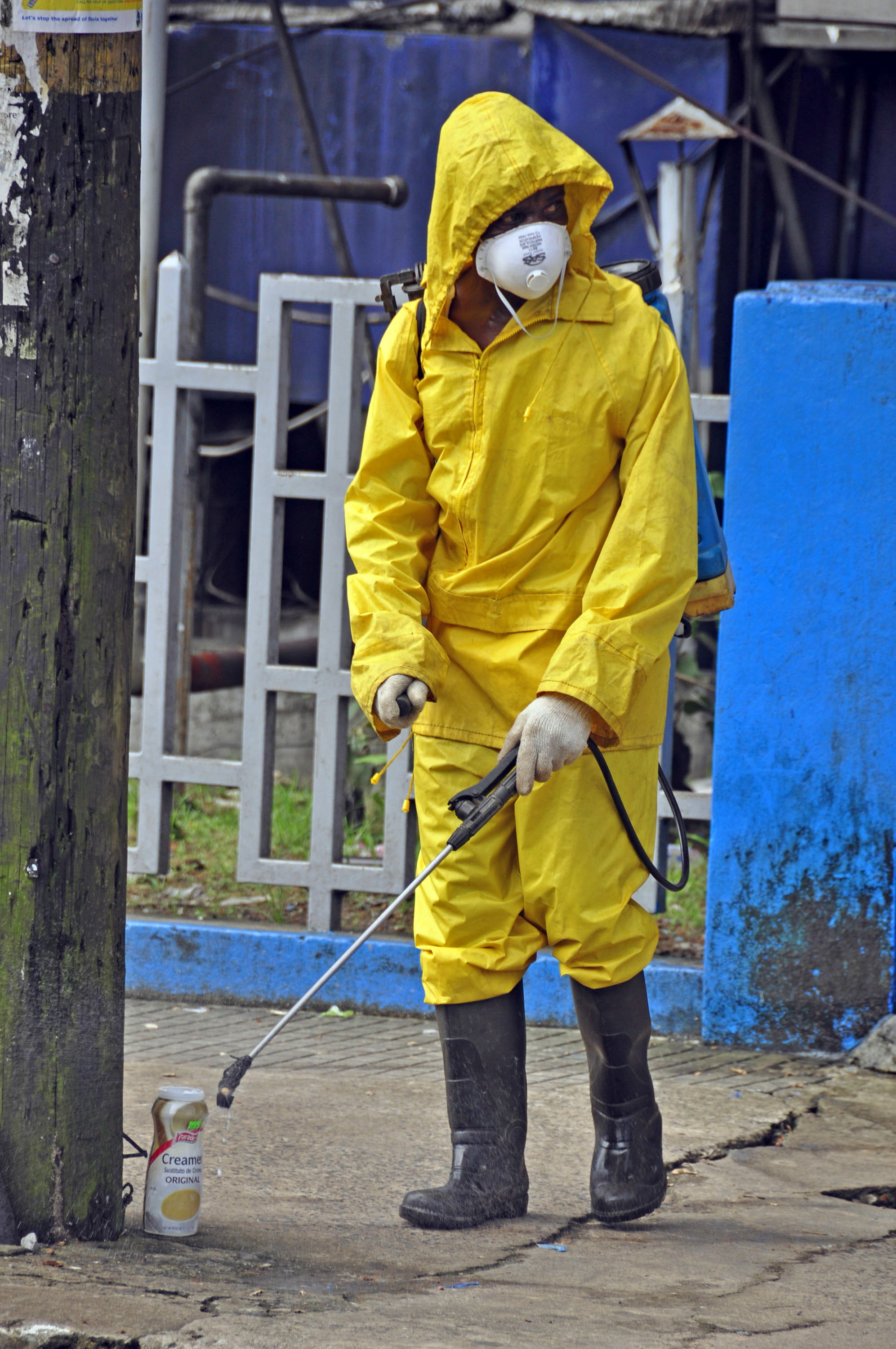 An employee  of the Monrovia City Corporation sprays disinfectant on a street, in front of a building in a bid to prevent the spread of  the deadly Ebola virus, in the city of Monrovia, Liberia, Friday, Aug. 1, 2014 .U.S. health officials warned Amer...