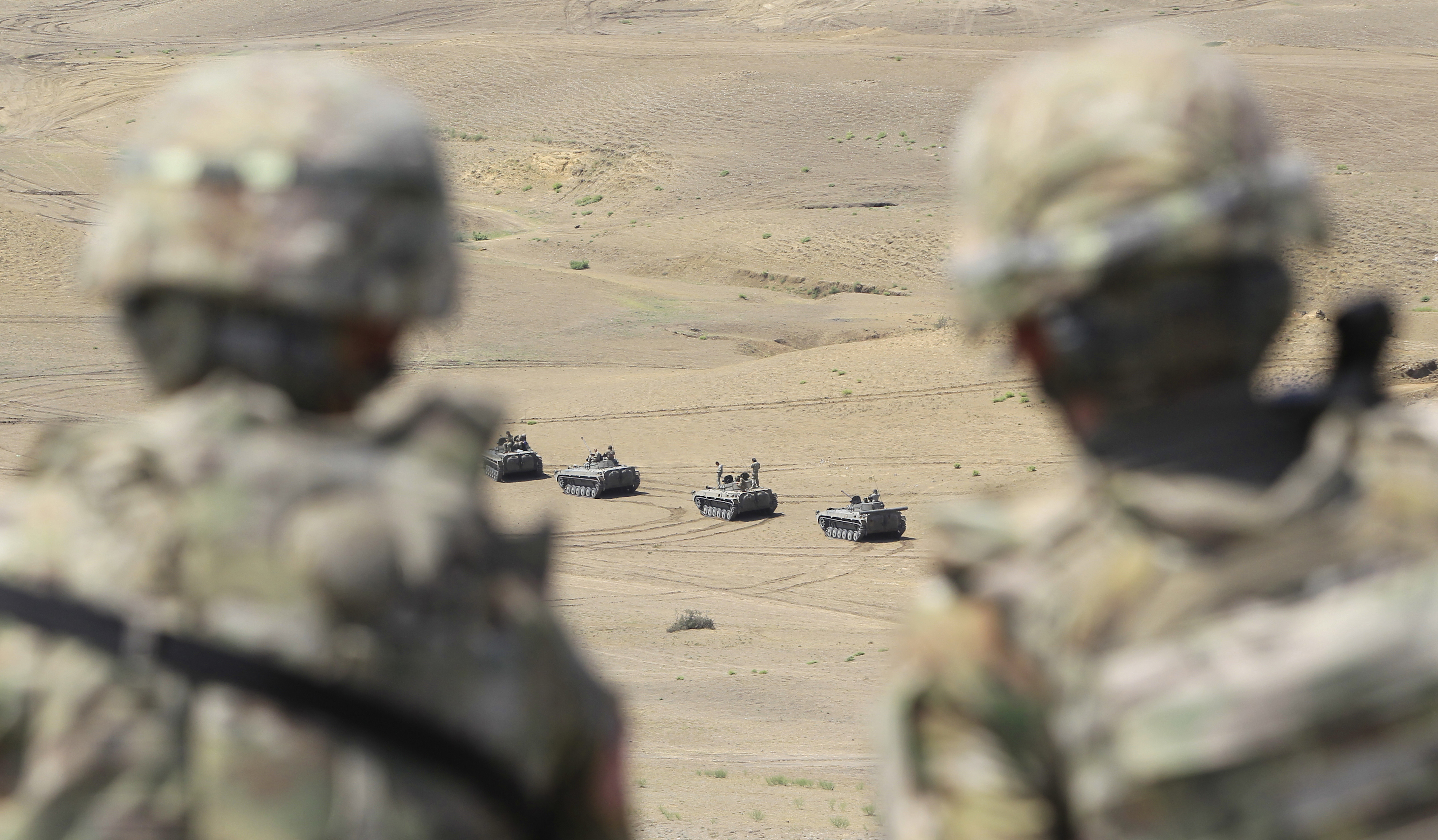 FILE - US soldiers watch as Georgian military vehicles take part in NATO-led Noble Partner 2017 multinational military exercises at the military base of Vaziani, outside Tbilisi, Georgia, Aug. 9, 2017.