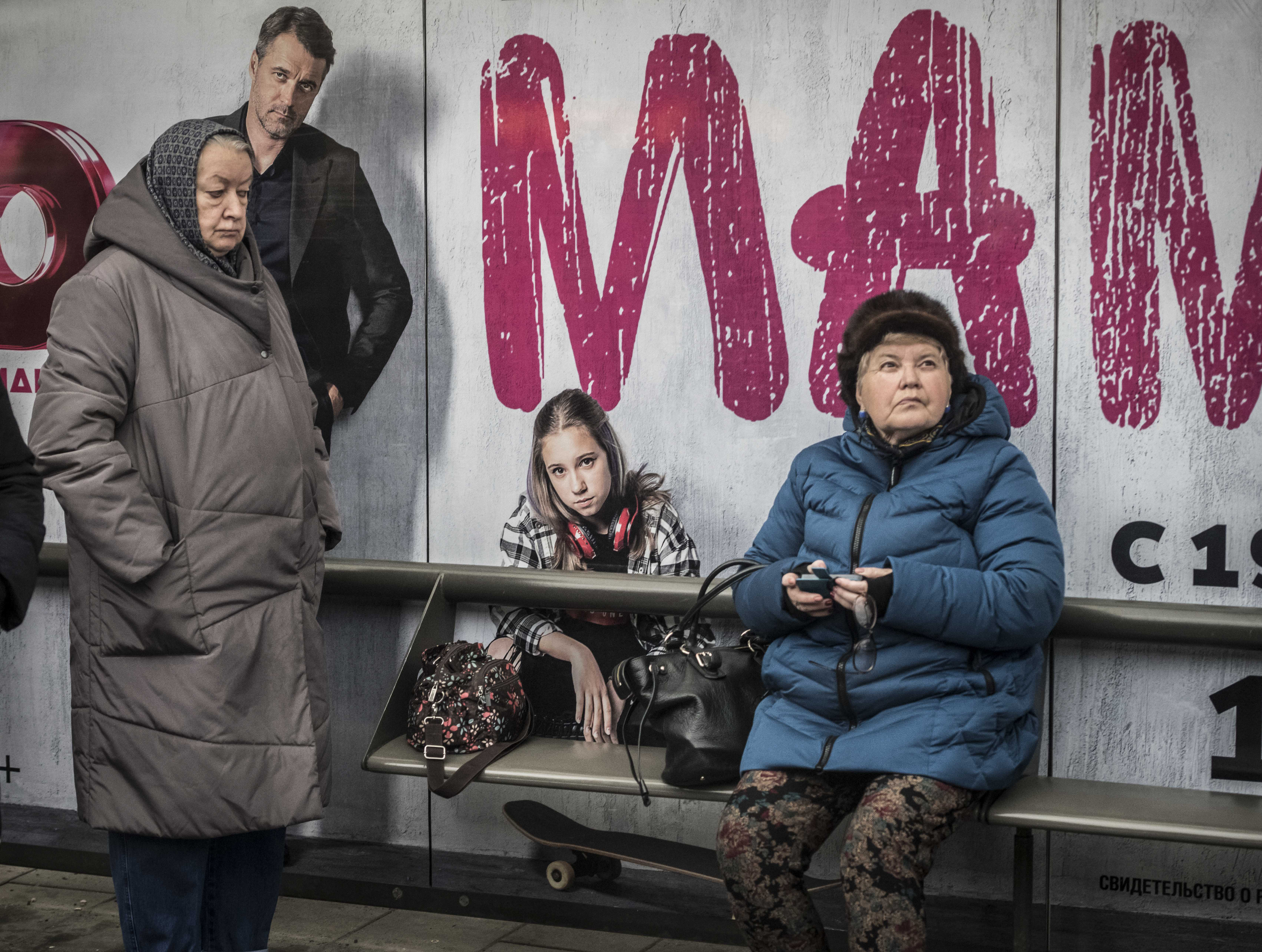 FILE - Two elderly women wait for their ride at a bus stop in Moscow, Nov. 1, 2018.