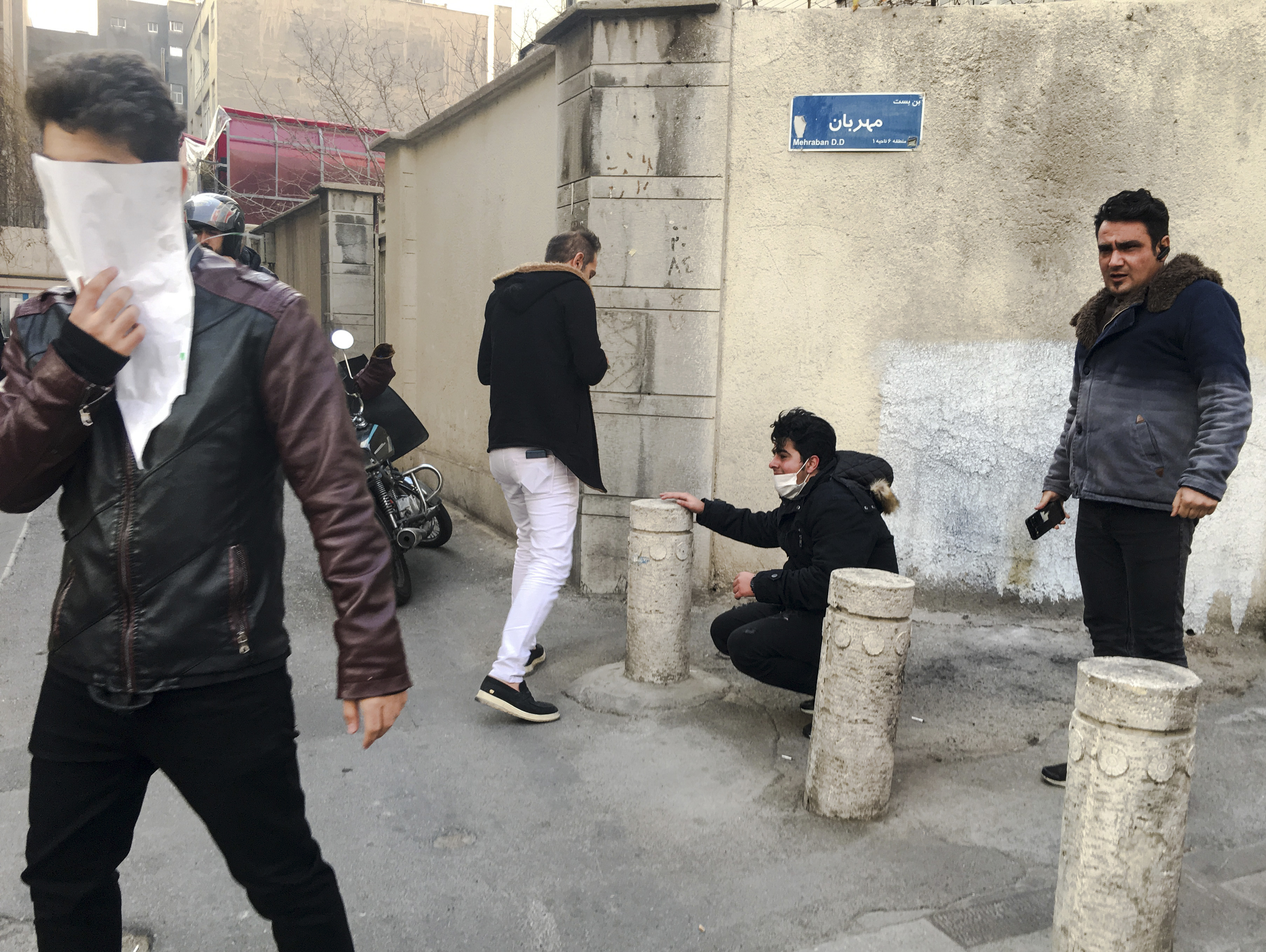 FILE - In this photo taken by an individual not employed by the Associated Press and obtained by the AP outside of Iran, people are affected by tear gas fired by anti-riot Iranian police to disperse demonstrators in a protest over Iran's weak economy...