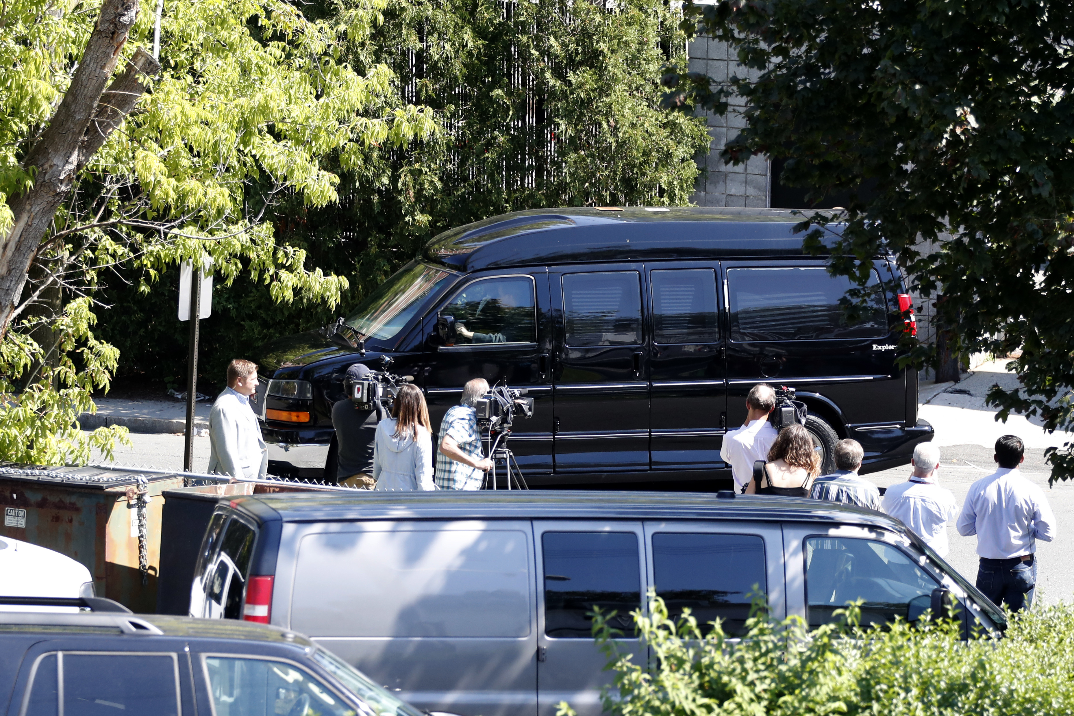 Reporters watch as Democratic presidential candidate Hillary Clinton's van leaves a FBI facility in White Plains, New York, after she received her first classified intelligence briefing as a leading presidential contender, Aug. 27, 2016.