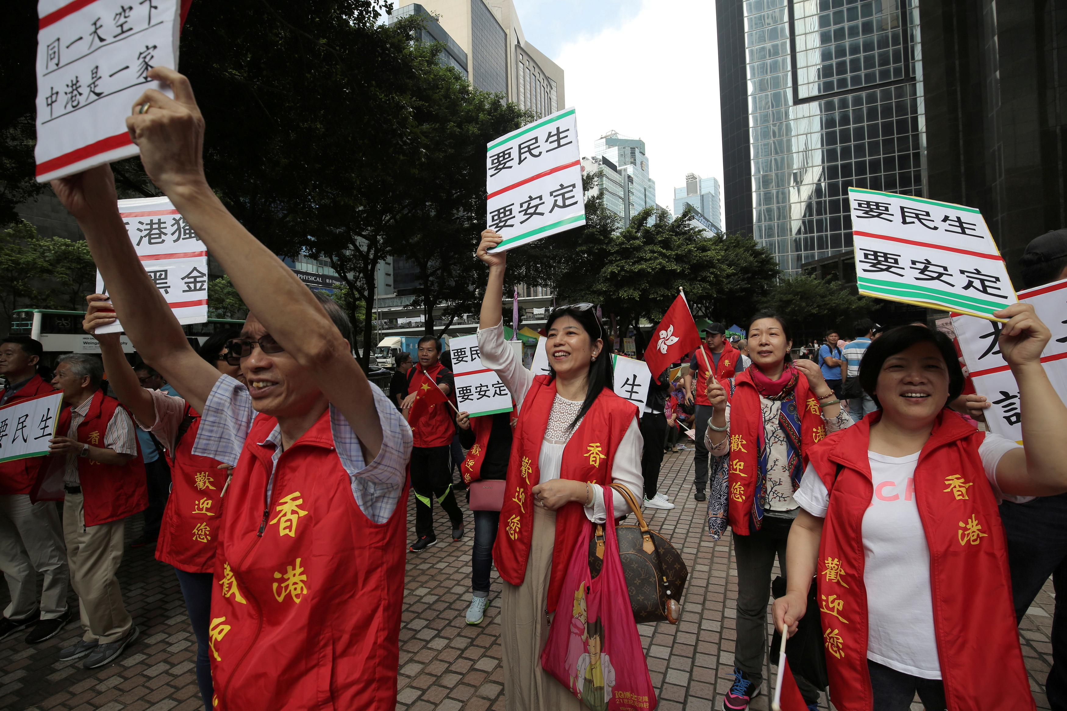 "Supporters of visiting Zhang Dejiang, the chairman of China's National People's Congress, hold placards which read ""Need livelihood, need stability"", in Hong Kong on May 18, 2016."