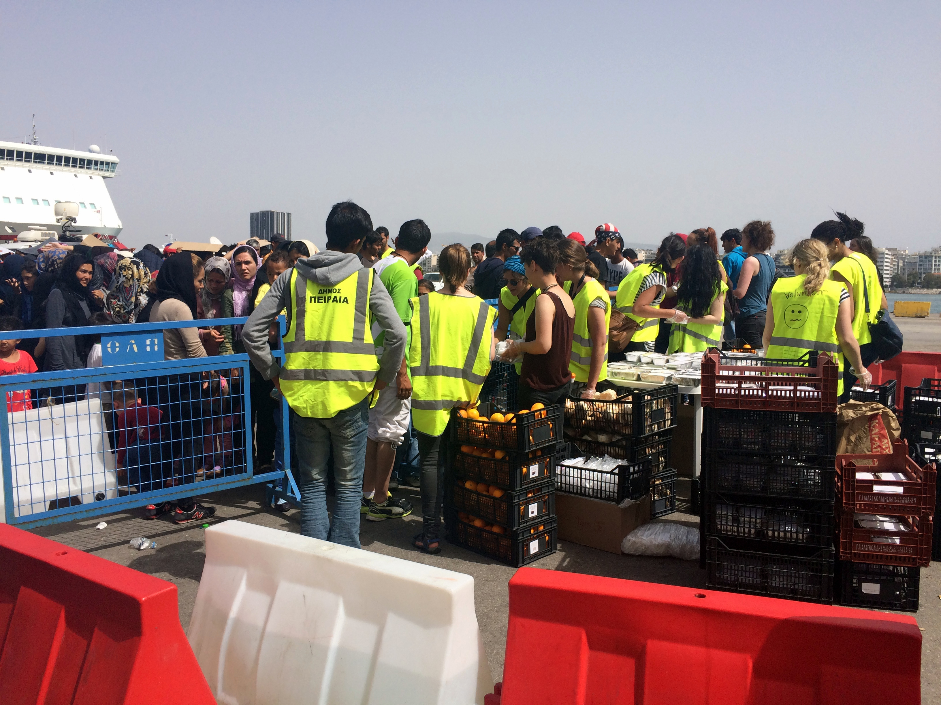 Aid workers distribute food to crowds of people camping on Piraeus port, many who have been there for a month, hoping the Macedonia border will open despite the fact that Macedonia continues to grow its border patrols, Athens, Greece, April 8, 2016. ...