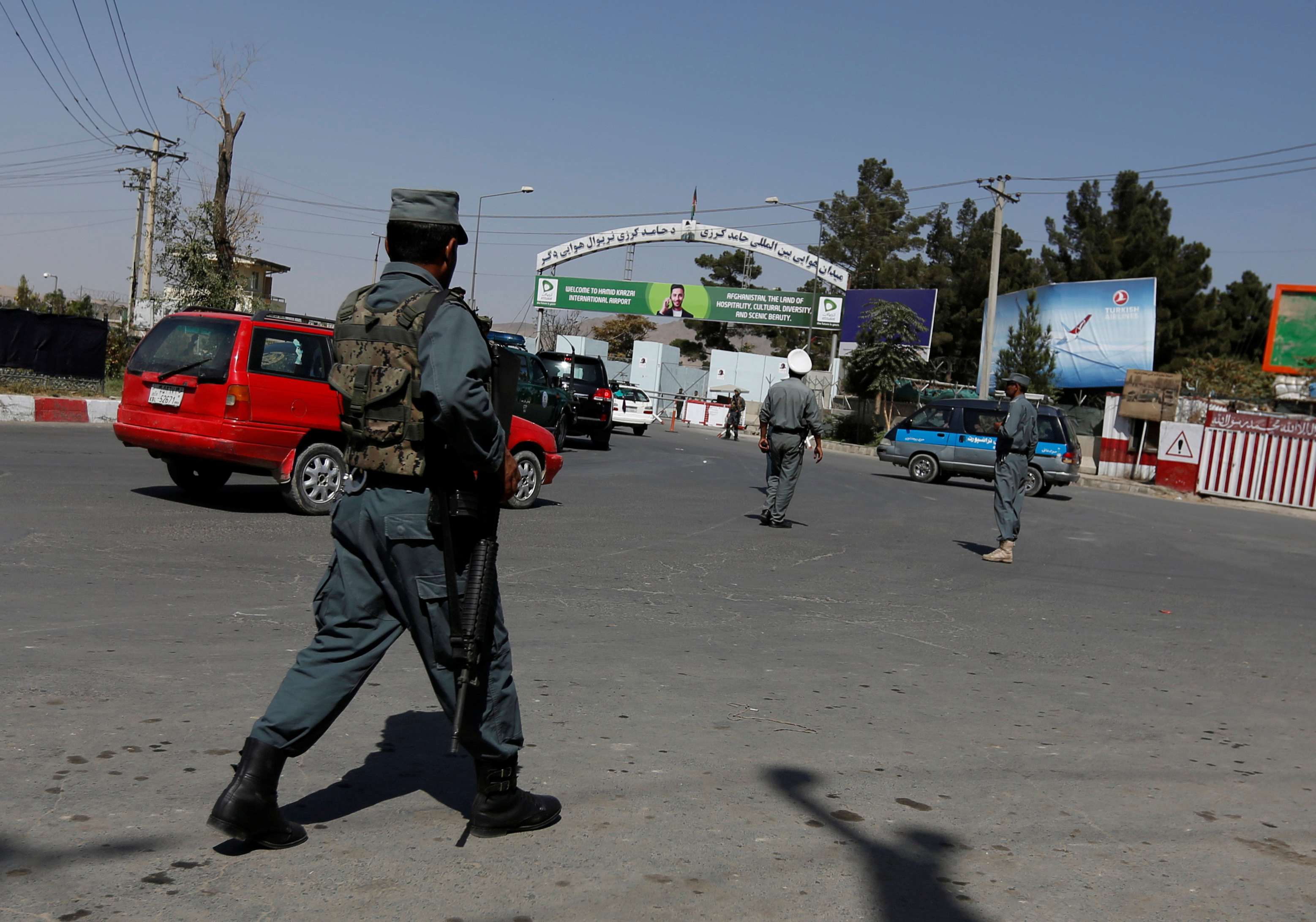 FILE - Afghan policemen stand guard outside of Kabul Airport after rockets exploded in Kabul, Afghanistan Sept. 27, 2017.