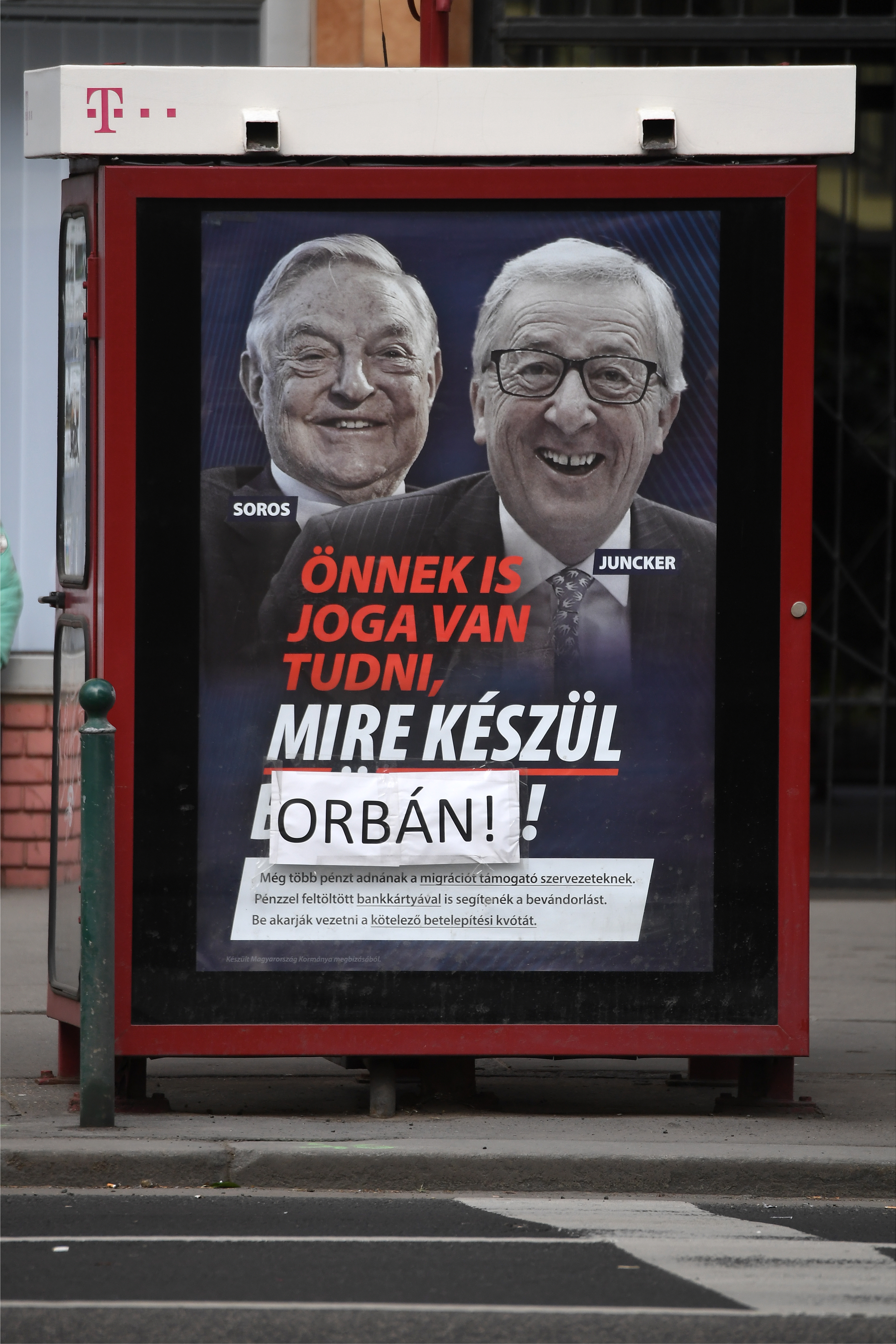 "A poster on a telephone booth shows  EC chief Jean-Claude Juncker, right, and Hungarian-born U.S. investor  George Soros and a slogan reading ""You too have a right to know what Brussels is preparing"" as the name ""Brussels"" is covered by the family na..."