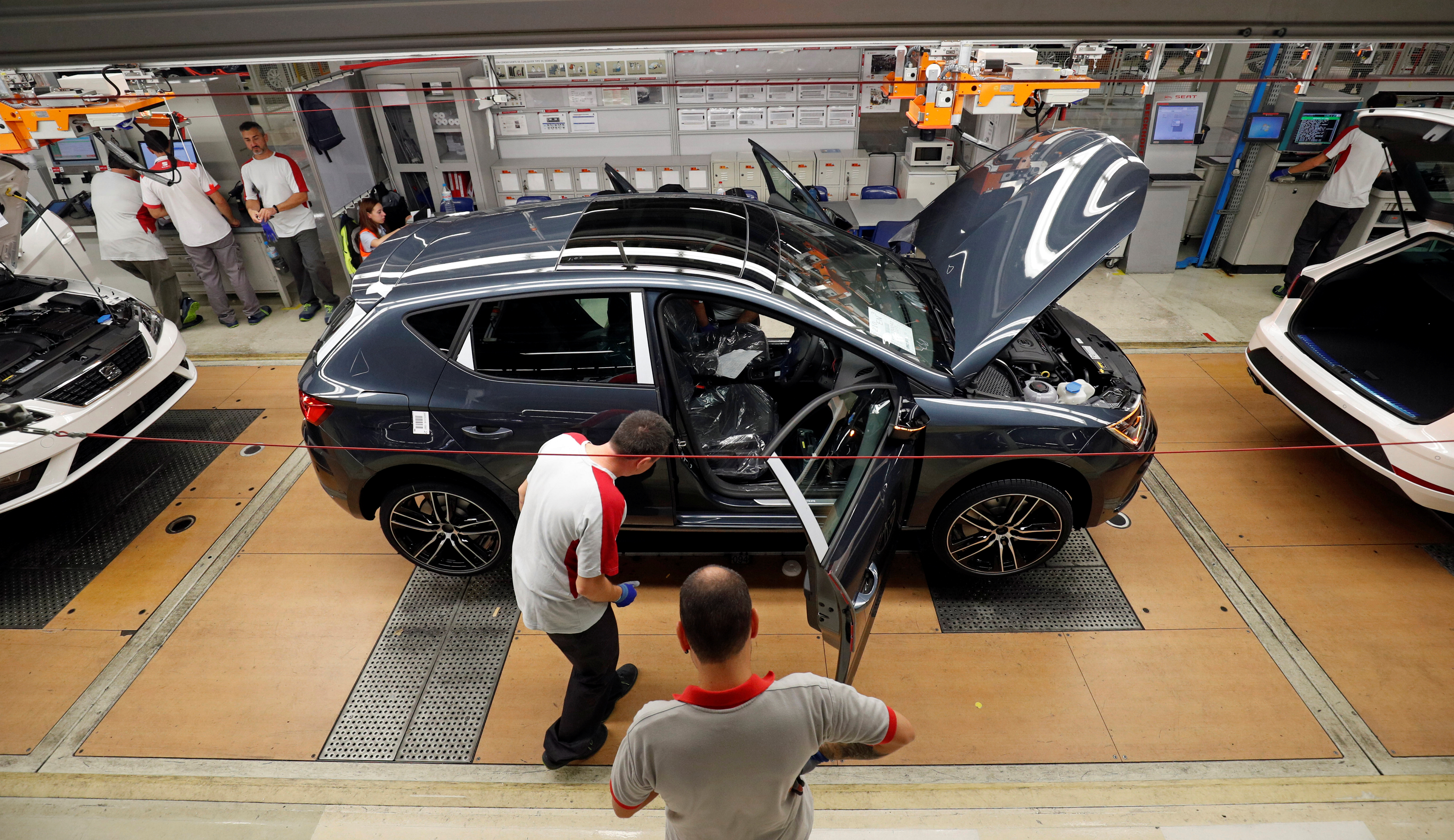 Workers put together vehicles on the assembly line of the SEAT car factory in Martorell, near Barcelona, Spain, Oct. 31, 2018.