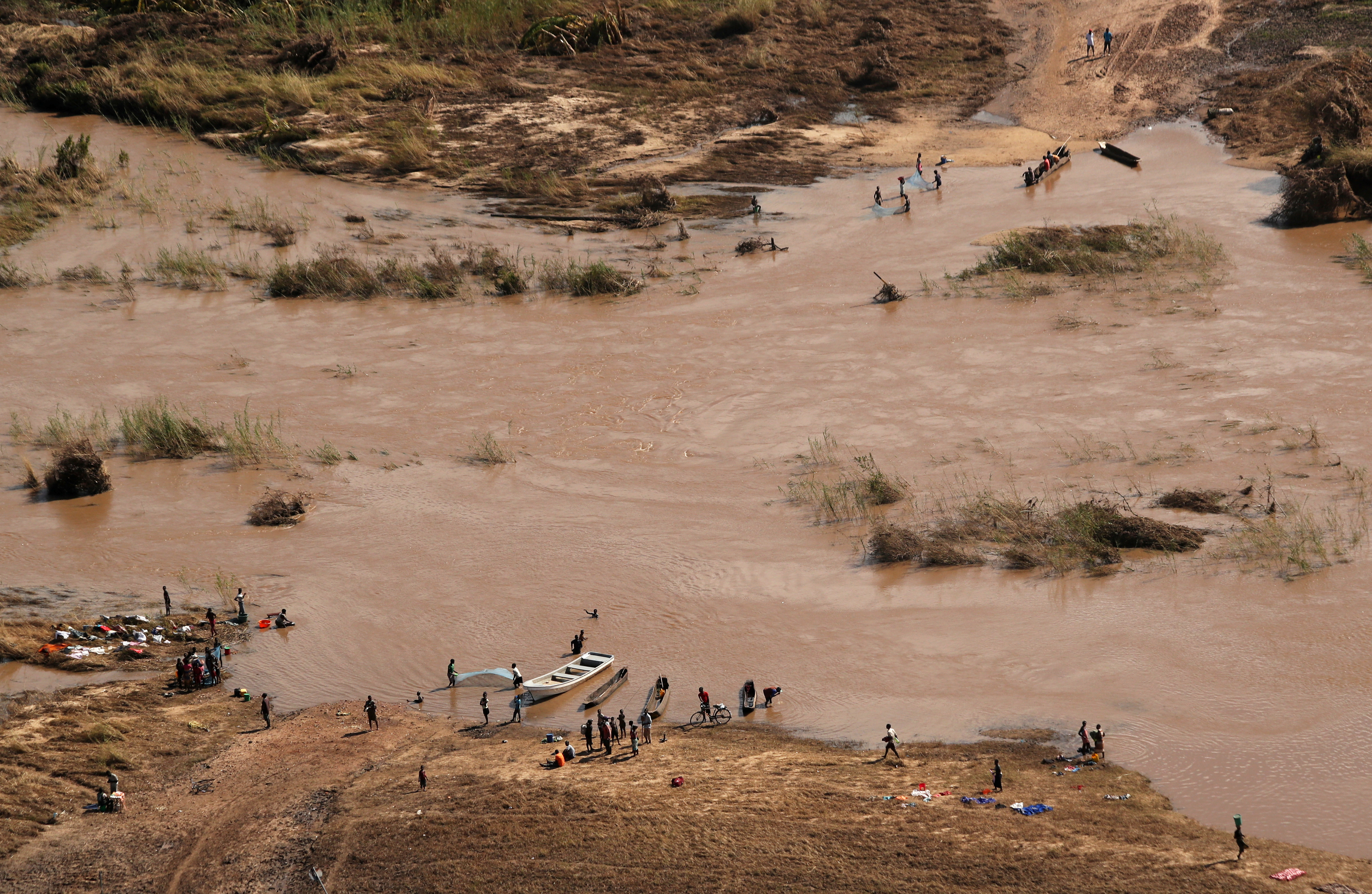 People stand on the banks where the bridge was washed away, in the aftermath of Cyclone Idai, near the village of John Segredo, Mozambique, March 24, 2019.