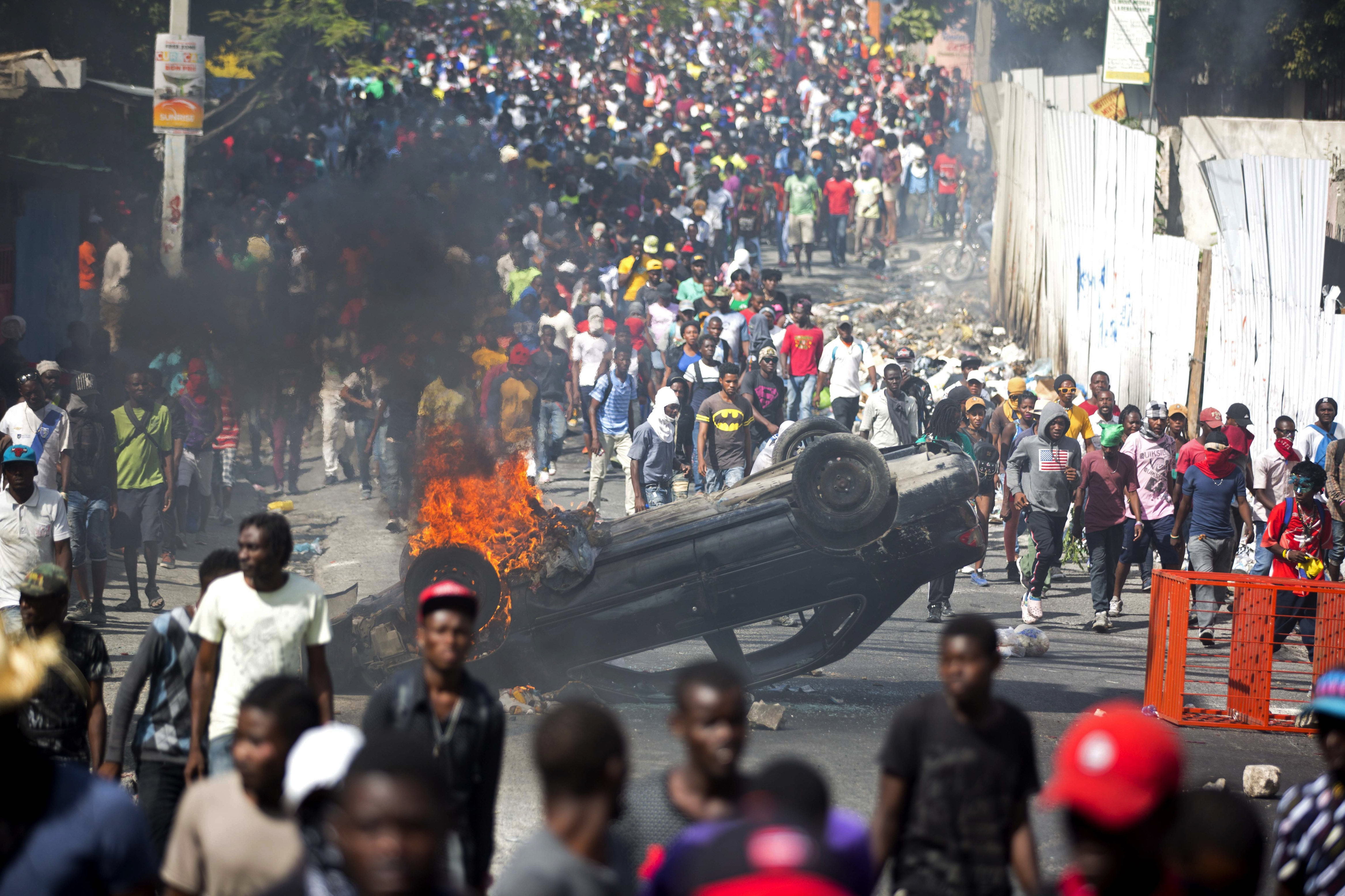 In this Feb. 12, 2019 file photo, an overturned car burns during a protest demanding the resignation of Haitian President Jovenel Moise in Port-au-Prince, Haiti.