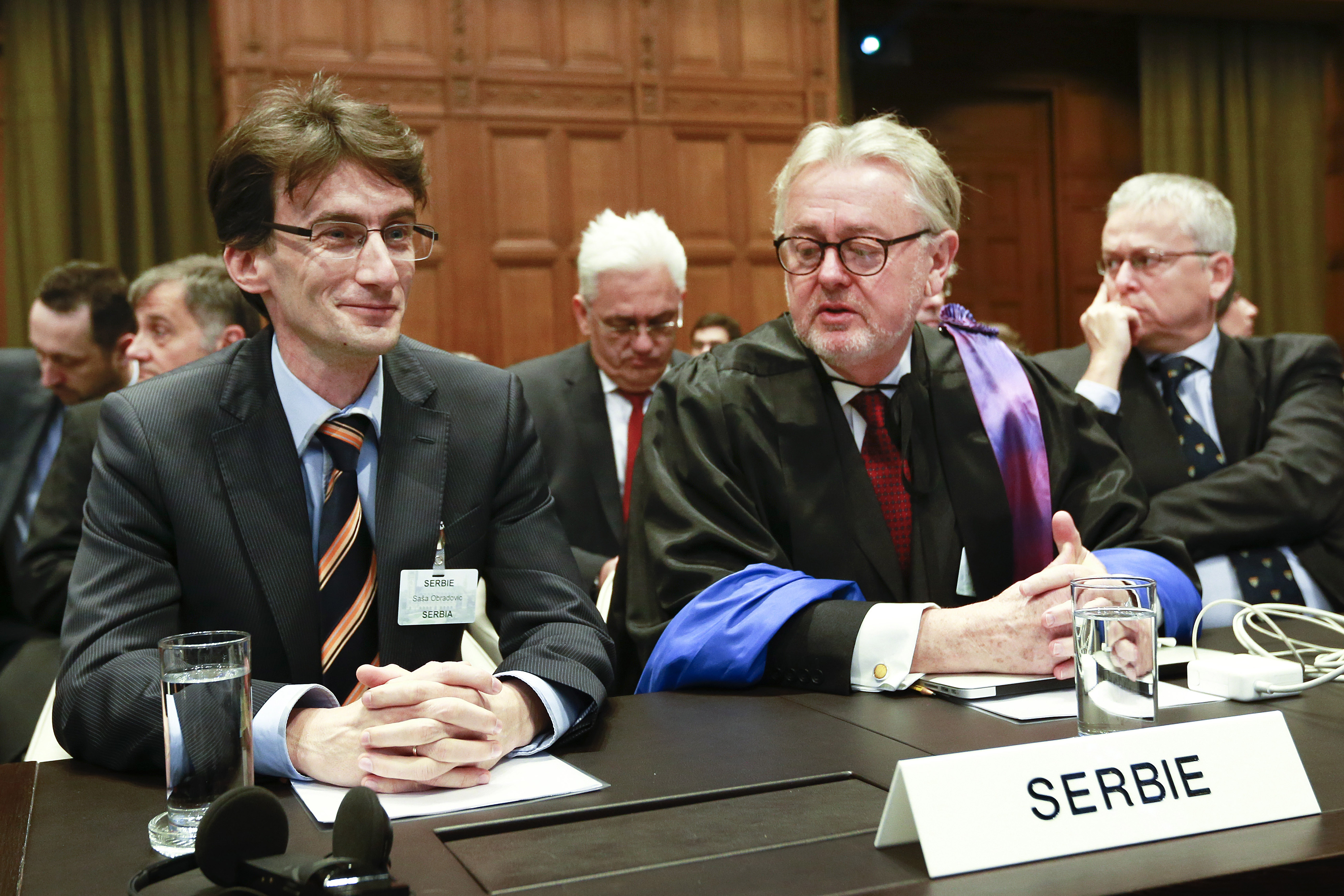 FILE - Members of the Serbian delegation, First Counsellor Sasa Obradovic, left, William Schabas, center and Andreas Zimmermann, right, await the start of public hearings at the International Court of Justice (ICJ) in The Hague,  Netherlands, March 3...