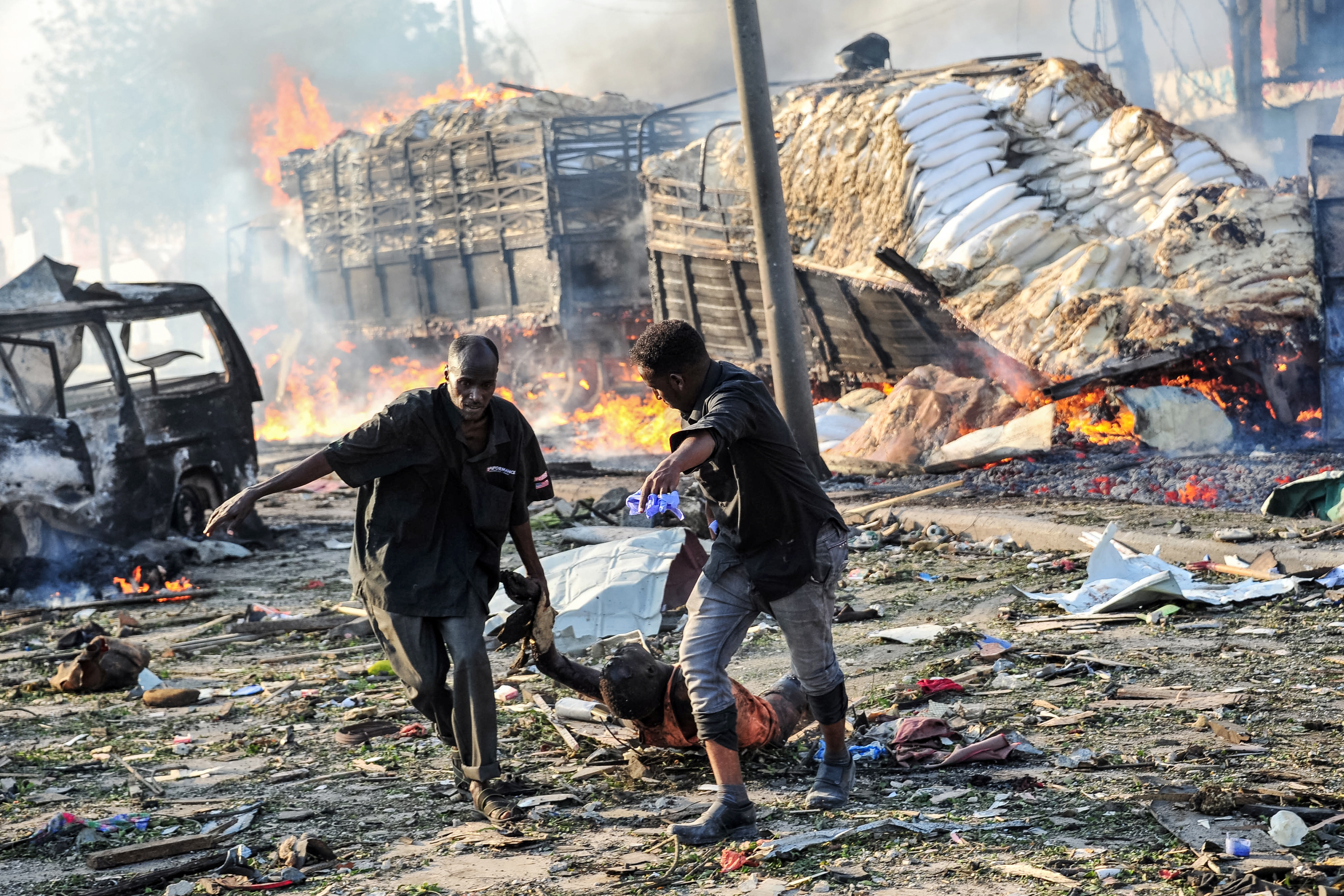 Two men carry the body of a victim following the explosion of a truck bomb in the center of Mogadishu, on Oct. 14, 2017.