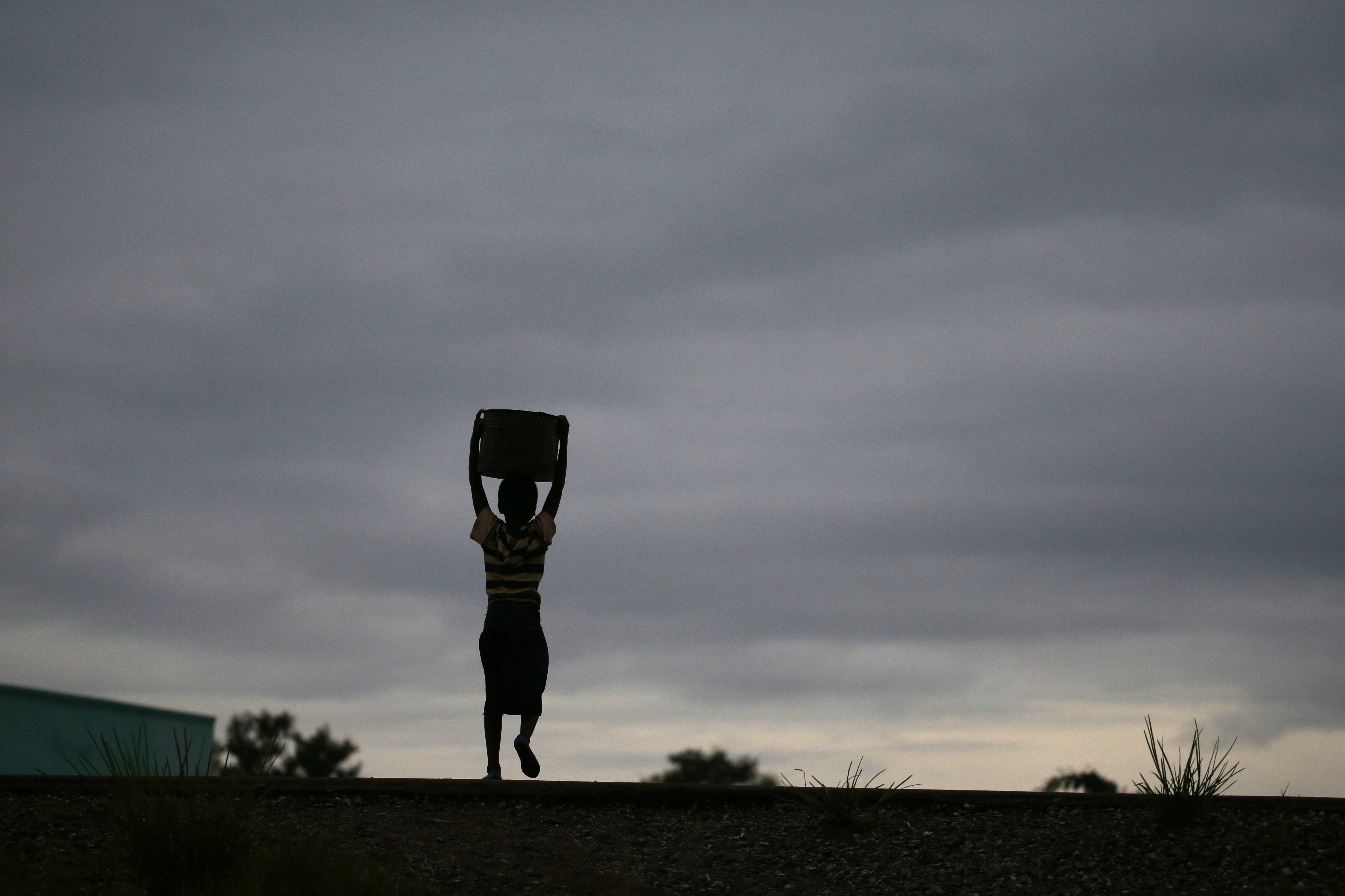 Storm clouds loom as a child carries water from a communal borehole near the capital Lilongwe, Malawi, Feb. 2, 2016. Floods and an El Nino-triggered drought have hit the staple maize crop