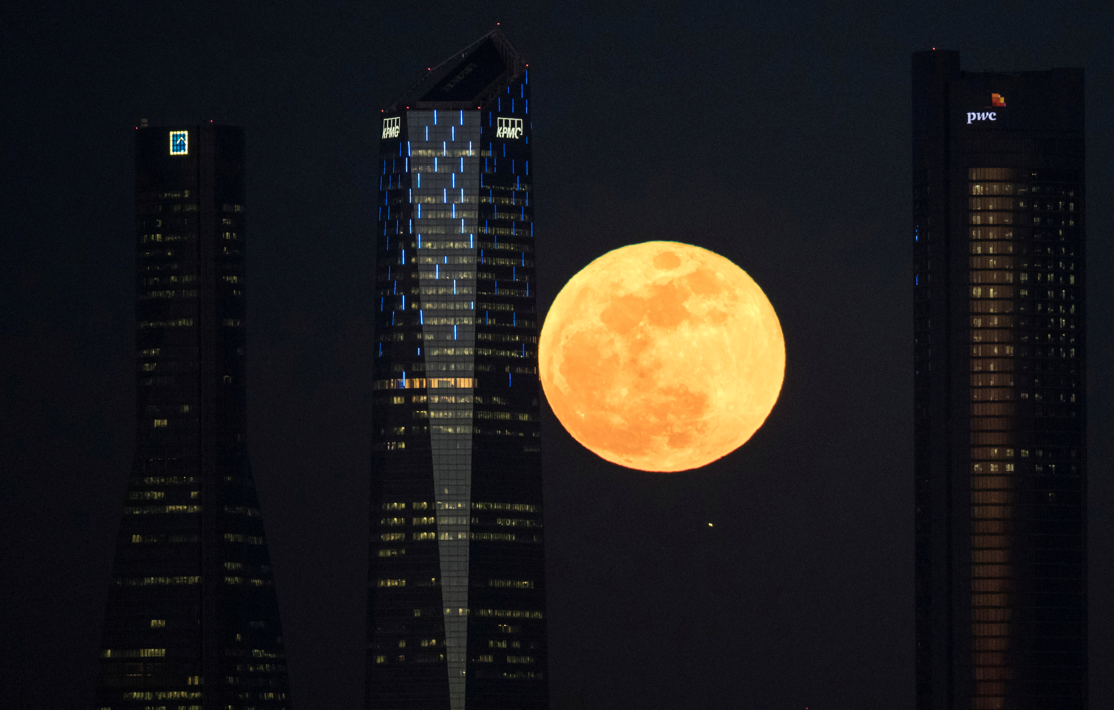 "A full moon ""supermoon"" rises in between four towers in a skyscrapers area in Madrid, Spain, January 31, 2018."