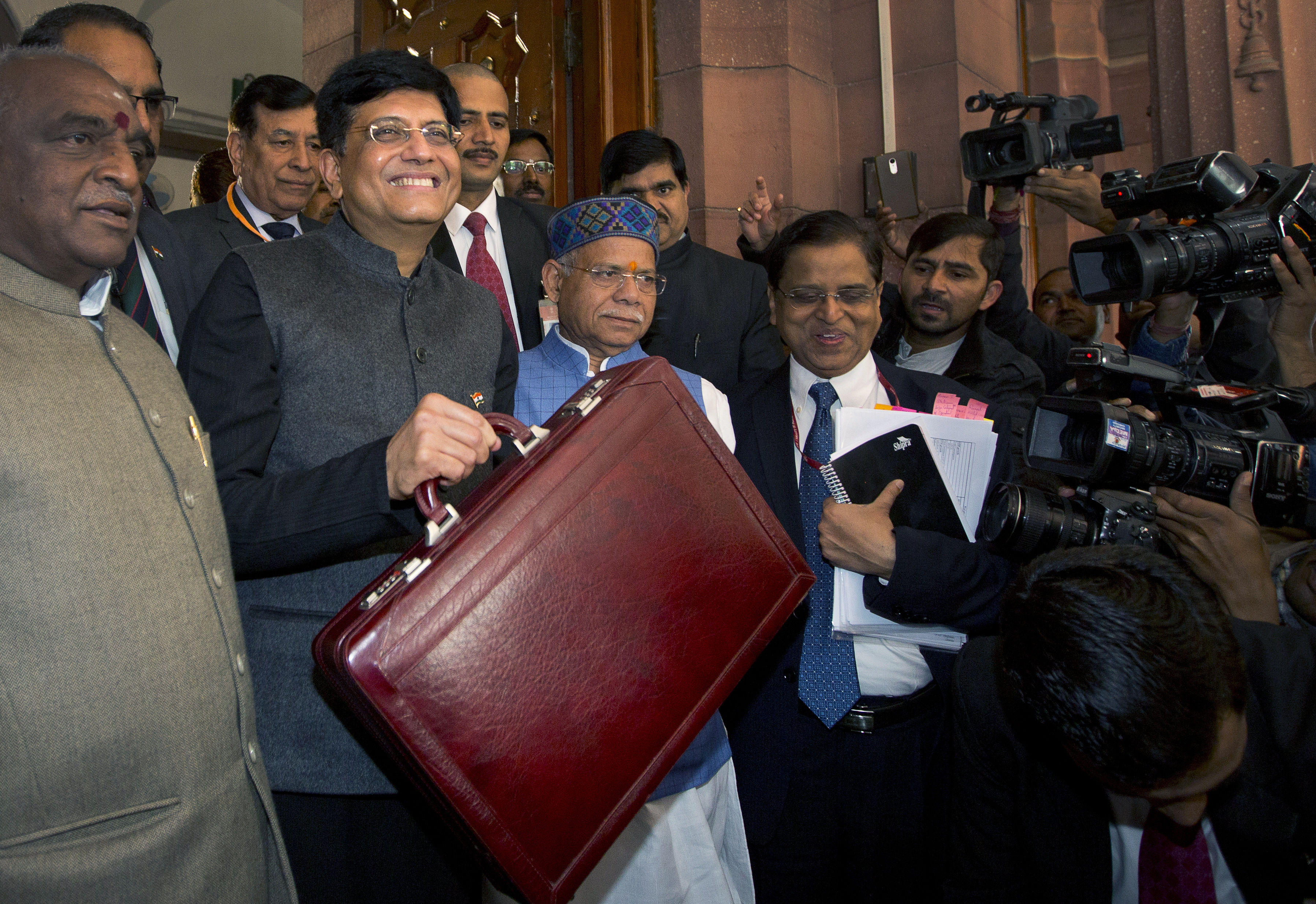 Interim Finance Minister Piyush Goyal, center, holds a briefcase containing federal budget documents with Junior Finance ministers Shiv Pratap Shukla, center right, and Pon Radhakrishnan, left, upon their arrival at the parliament house in New Delhi,...