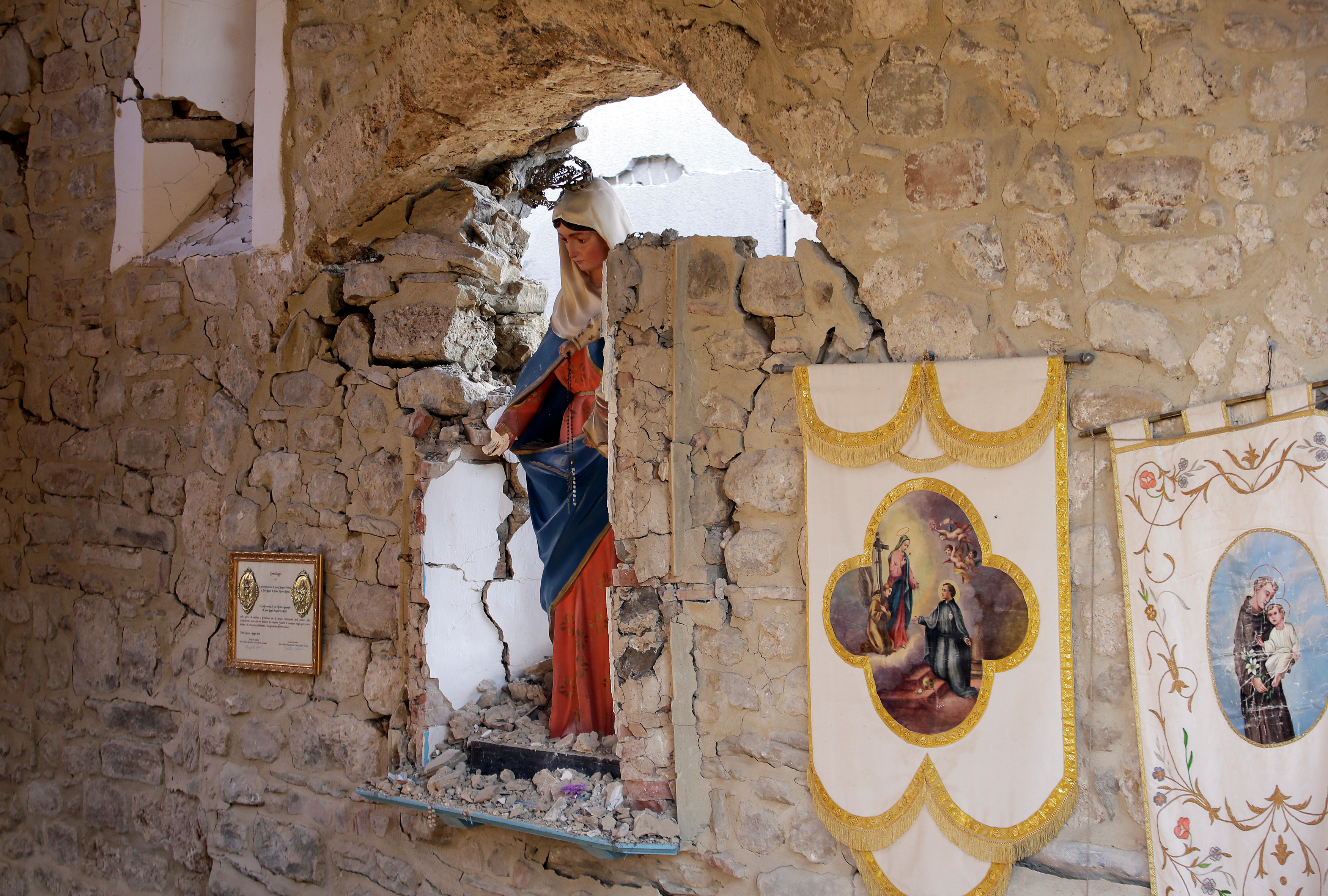 A Virgin Mary statue is seen in cemetery following an earthquake at Sant' Angelo near Amatrice, central Italy, Aug. 26, 2016.