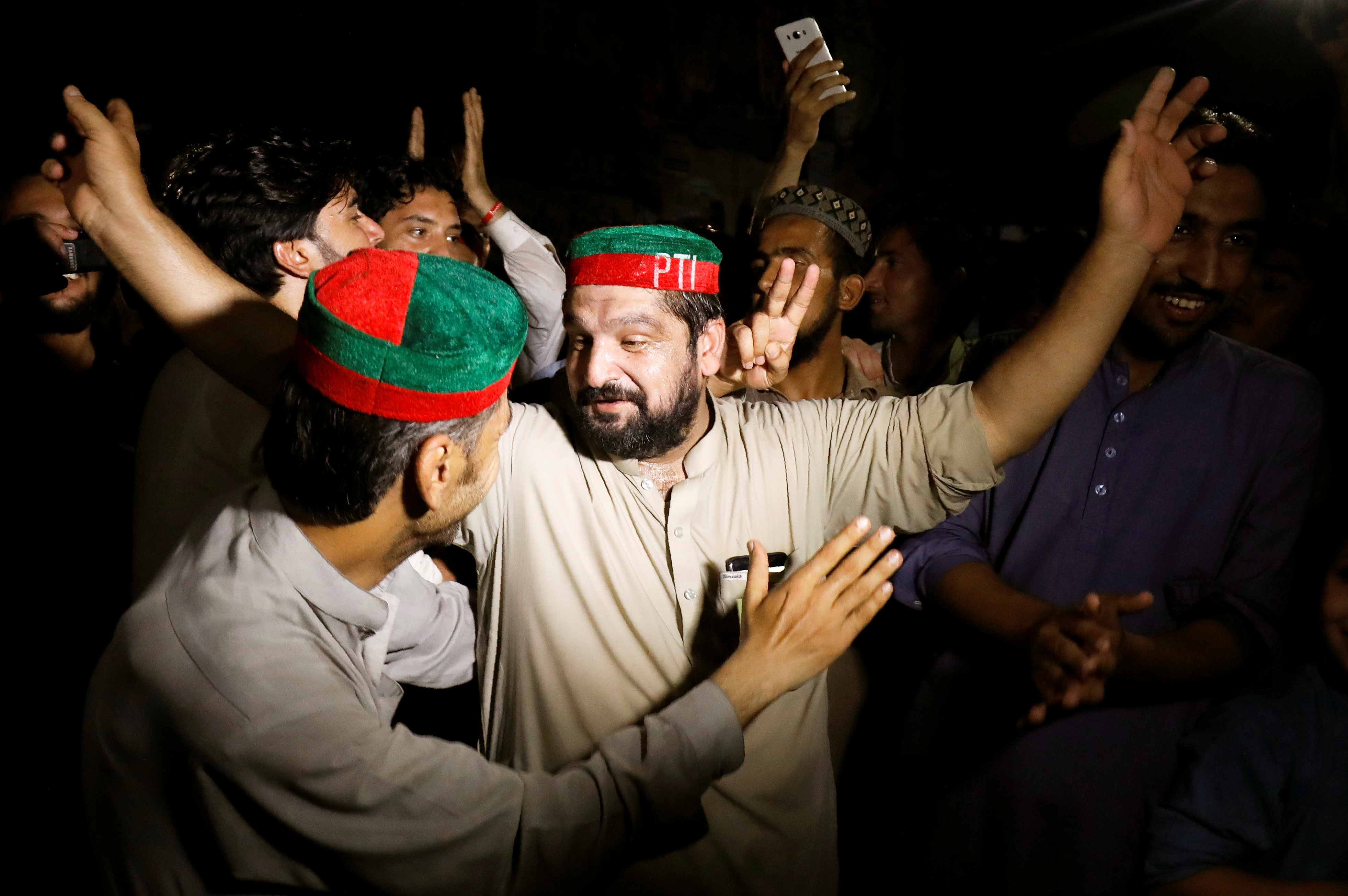 Supporters of Imran Khan, chairman of Pakistan Tehreek-i-Insaf (PTI) gesture to celebrate after Khan was elected as Prime Minister, in Peshawar, Pakistan, Aug. 17, 2018.