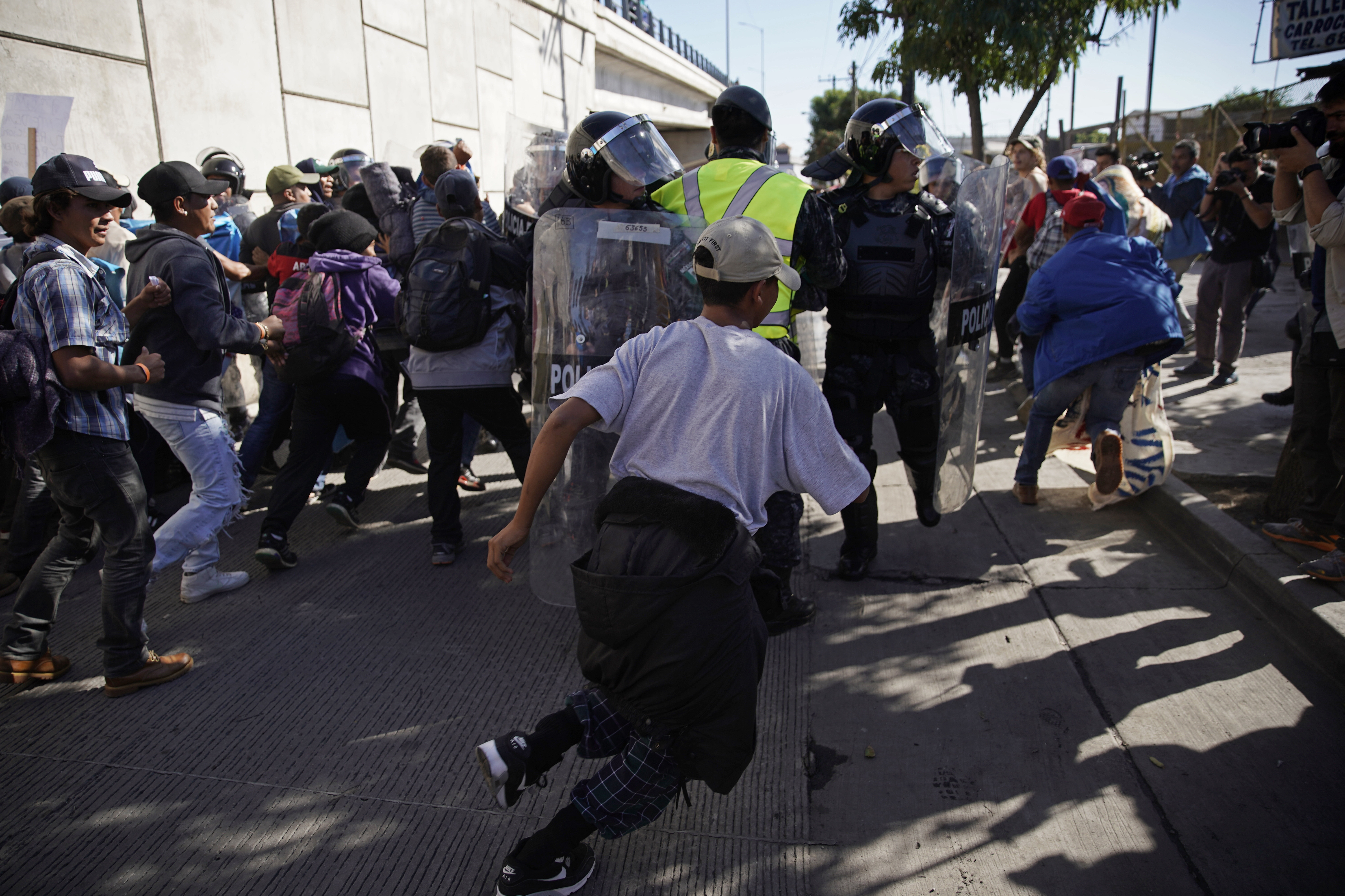 Migrants break past a line of police as they run toward the Chaparral border crossing in Tijuana, Mexico, Nov. 25, 2018, near the San Ysidro entry point into the U.S.