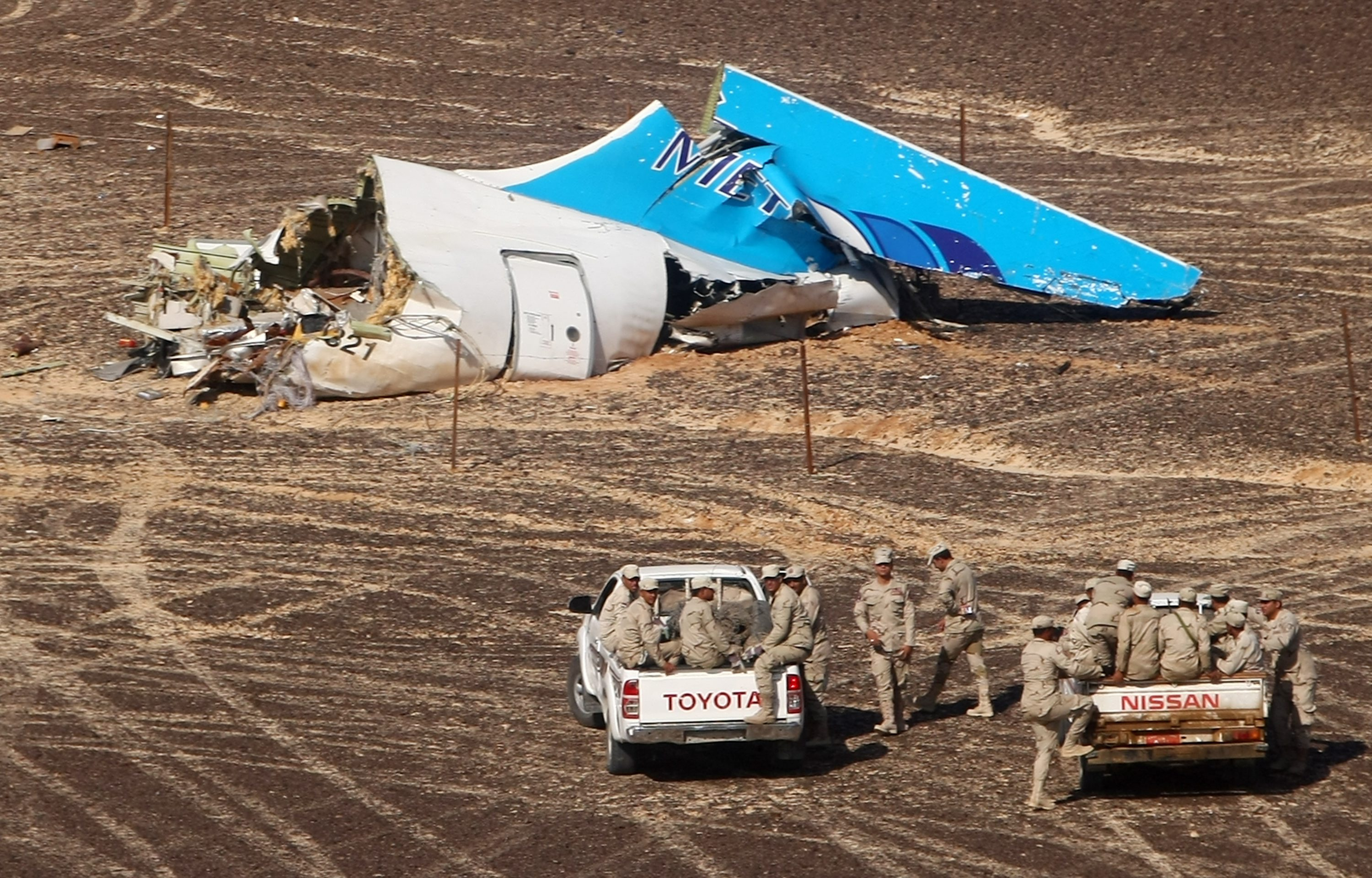 In this photo made available Nov. 2, 2015, and provided by Russian Emergency Situations Ministry, Egyptian military forces approach a plane's tail at the wreckage of a passenger jet bound for St. Petersburg in Russia that crashed in Hassana, Egypt, N...
