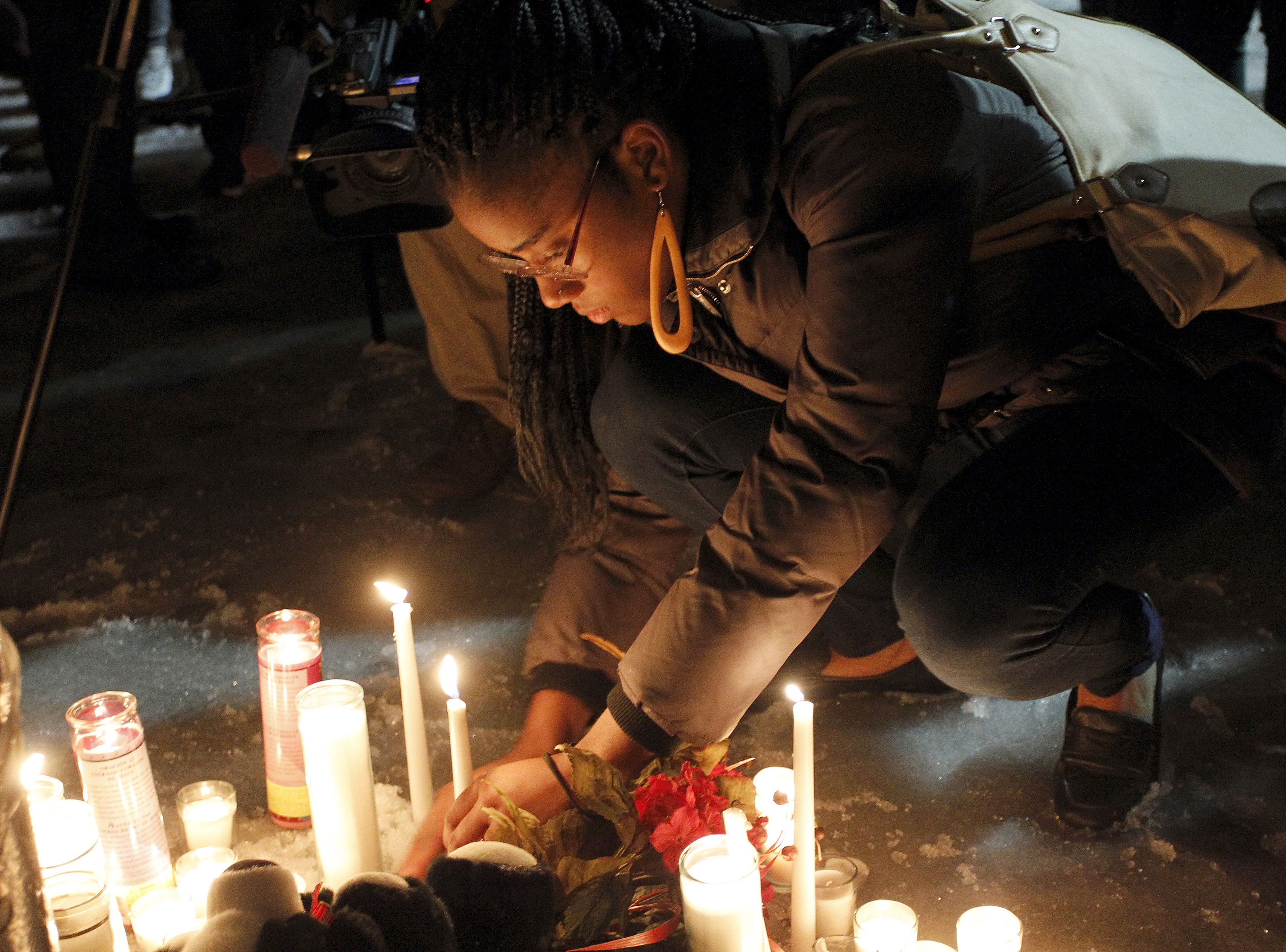 People place candles in a make-shift memorial as they attend a vigil in honor of Bettie Jones, a mother of five and college student Quintonio LeGrier, at Gwendolyn Brooks Academy in Chicago, Illinois, Dec. 29, 2015.