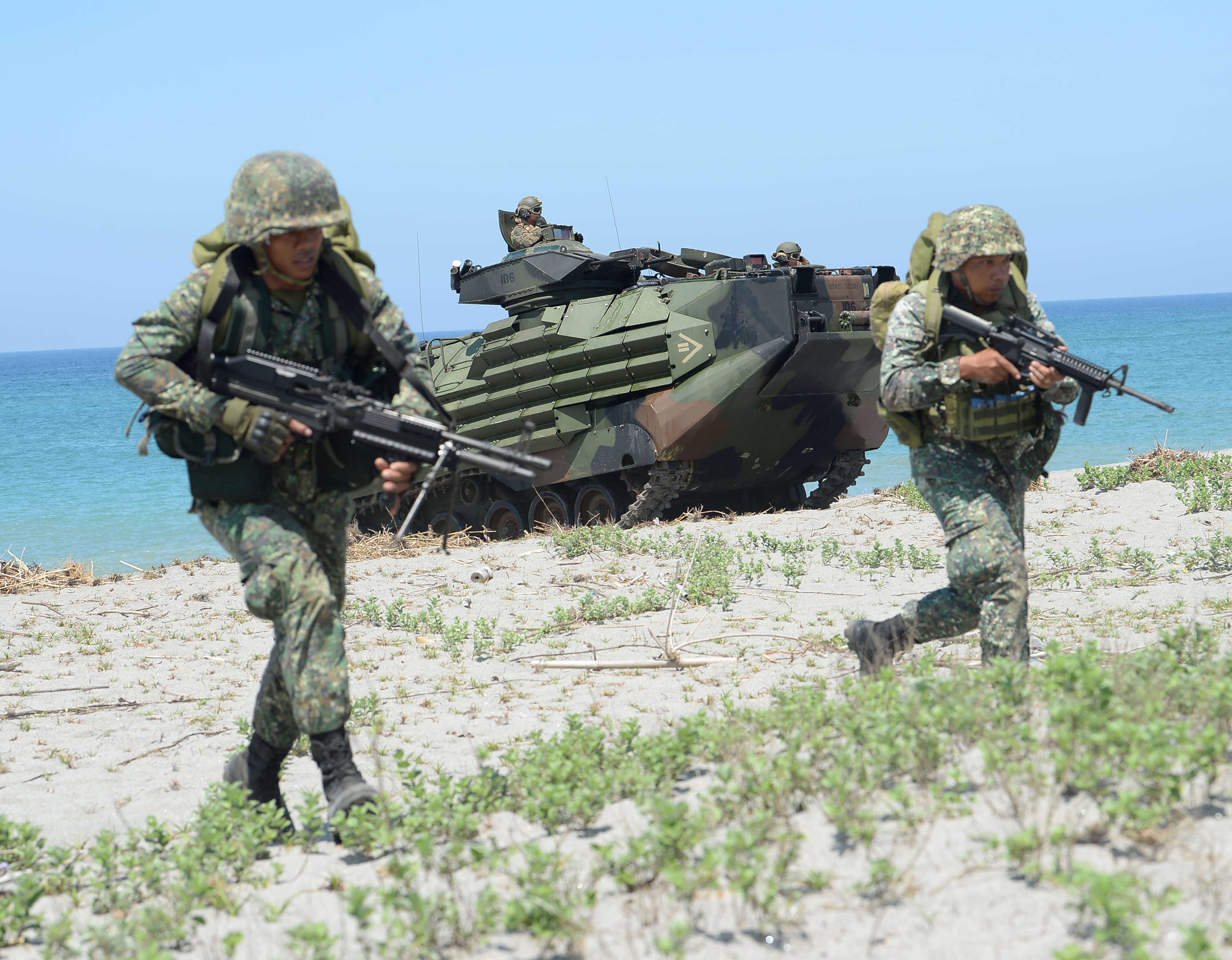 Philippine marines take position next to US Marines Amphibious Assault Vehicles (AAV) during an amphibious landing exercise at the beach of the Philippine navy training center facing the South China Sea in San Antonio town, Zambales province, north o...