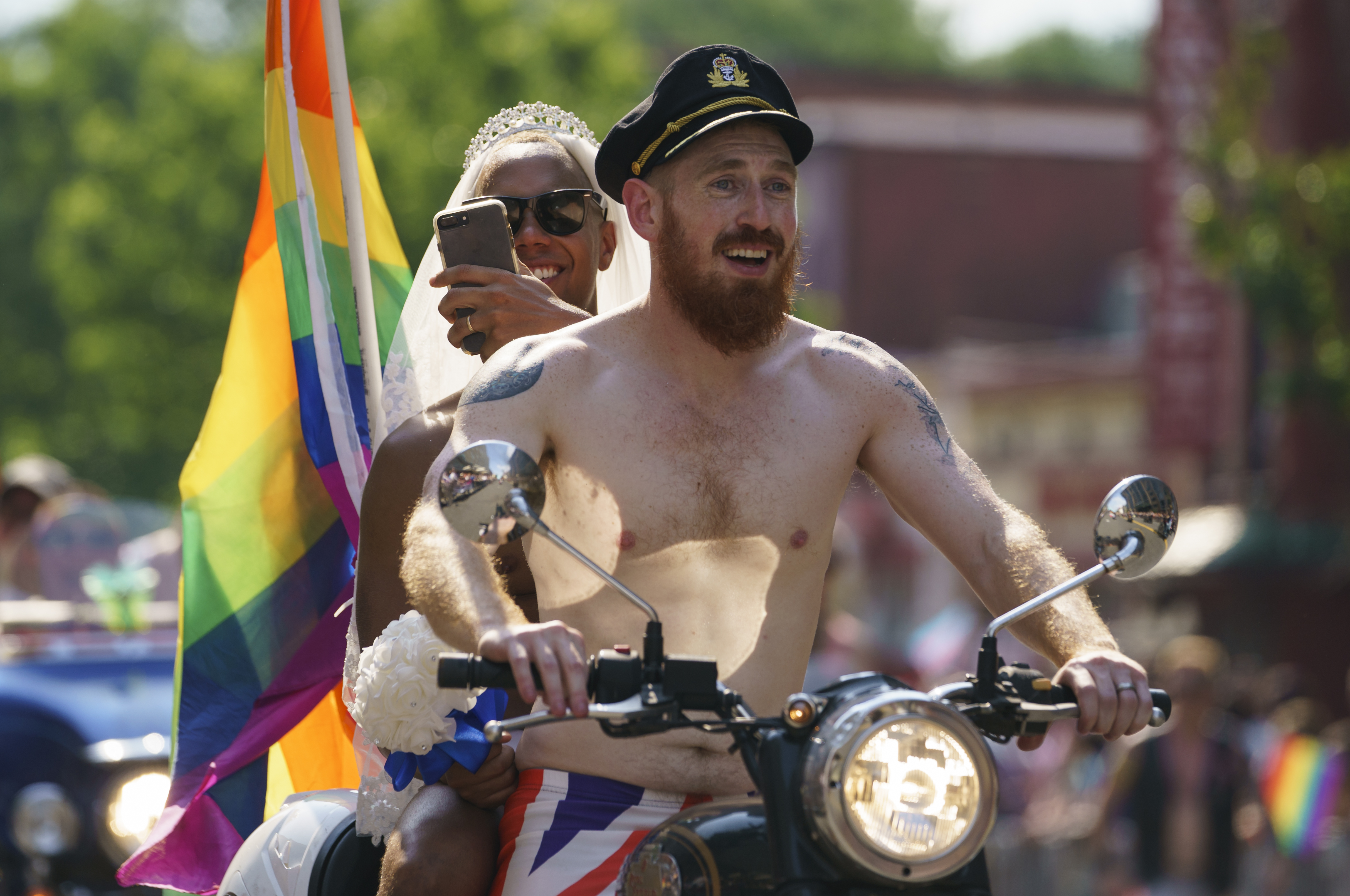 Scott Simpson, foreground, and his husband, Michael Clarke, ride with the Out Riders Women's Motorcycle Club, going as Prince Harry and Meghan Markle, in the Capital Pride Parade in Washington, June 9, 2018.
