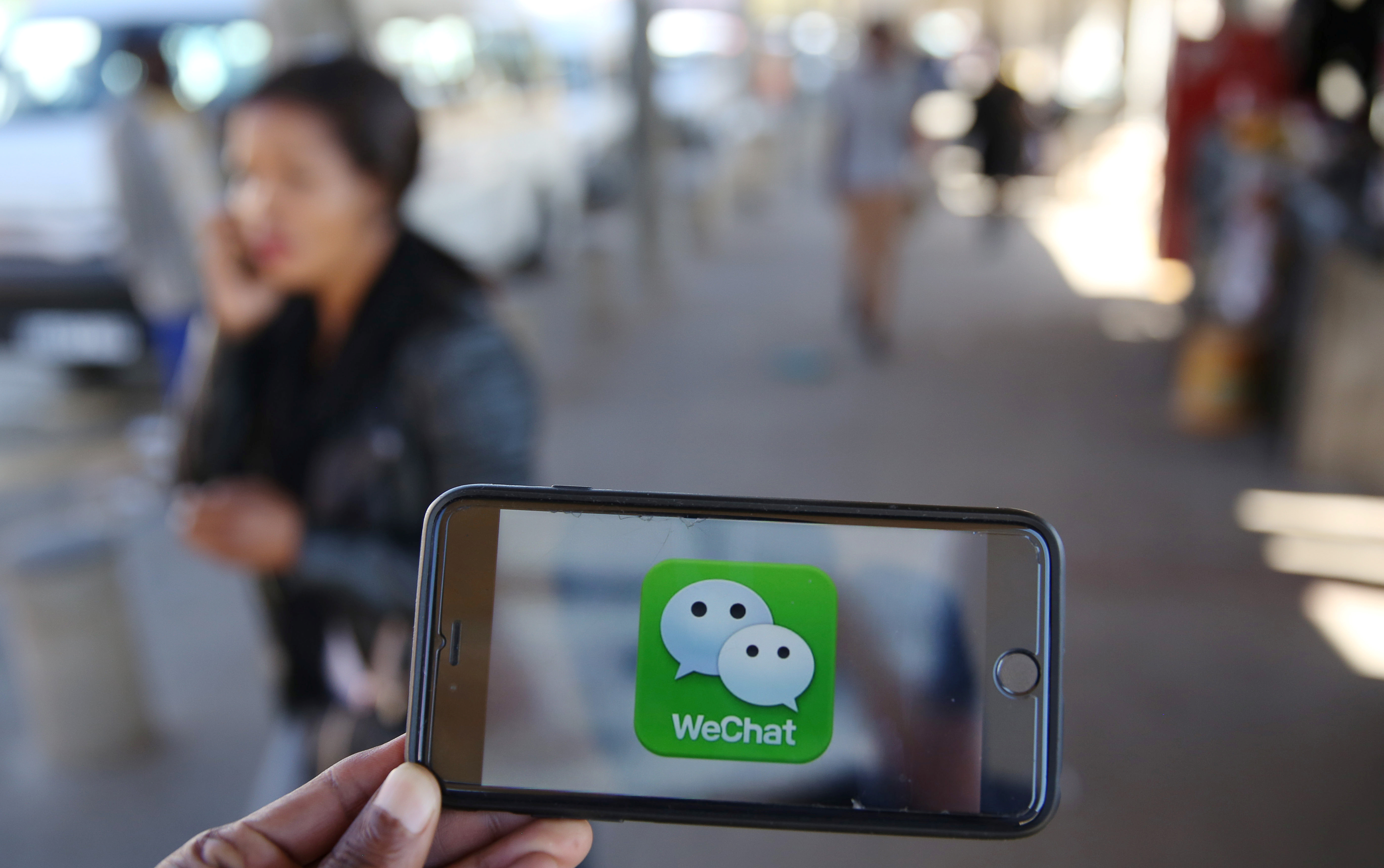 A WeChat logo is displayed on a mobile phone as a woman walks past as she talks on her mobile phone at a taxi rank in this picture illustration taken July 21, 2016. Picture taken July 21, 2016.