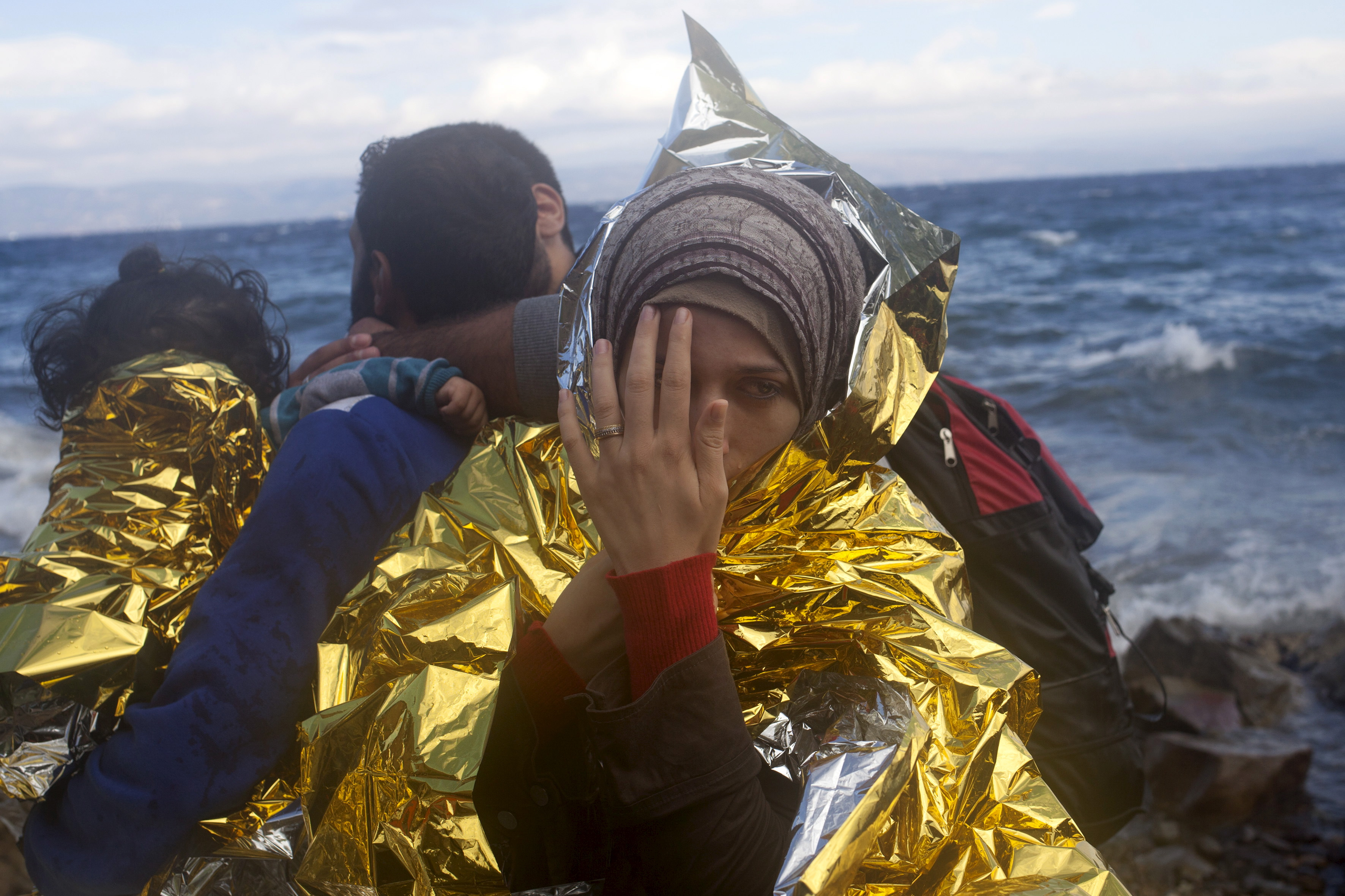 A Syrian refugee wrapped in a thermal blanket looks on, following her arrival on an overcrowded dinghy on the Greek island of Lesbos after crossing a part of the Aegean Sea from the Turkish coast, Sept. 30, 2015.