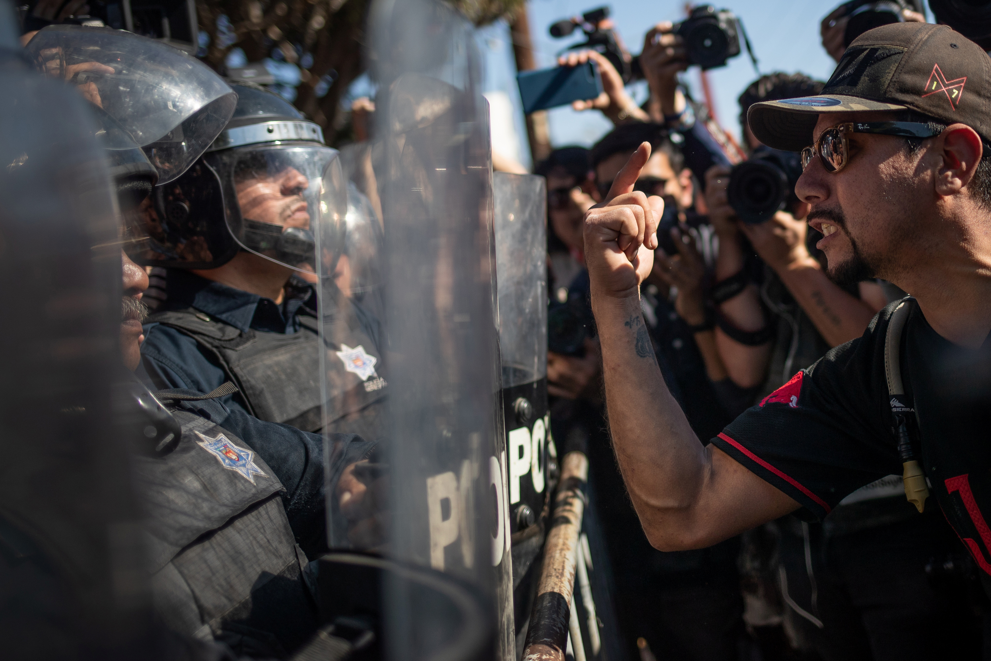 A demonstrator, part of a protest march against migrants, shouts towards a line of police in riot gear who were standing guard over a temporary shelter housing a caravan from Central America trying to reach the U.S., in Tijuana, Mexico, Nov. 18, 2018...