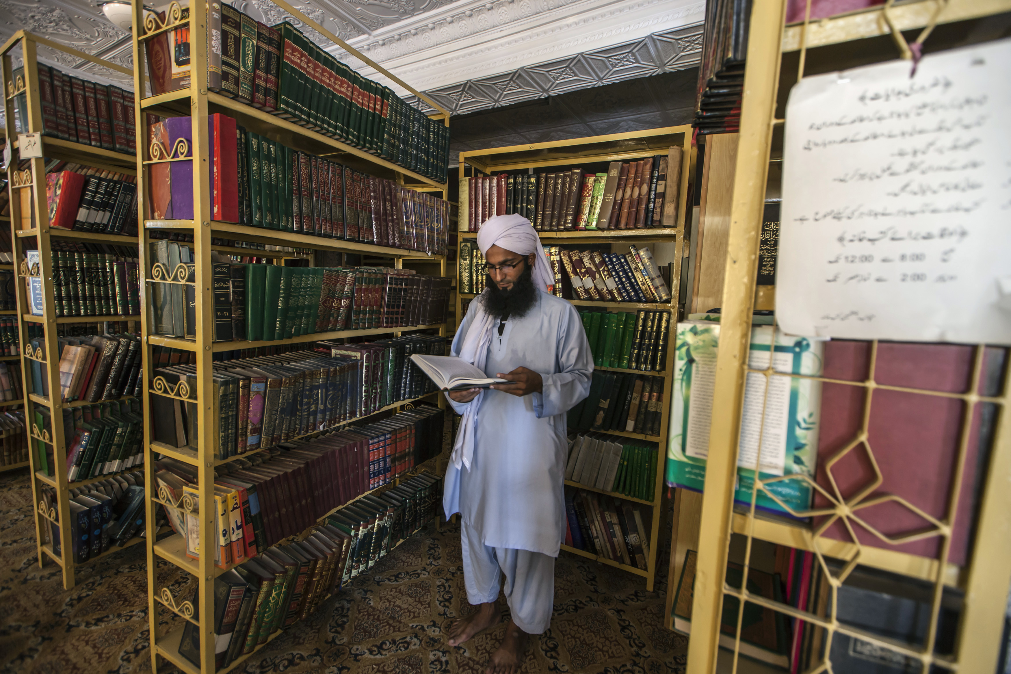 A Pakistani religious teacher refers to a book at a library at Darul Uloom Haqqania, an Islamic seminary in Akora Khattak, Khyber Pakhtunkhwa province, Sept. 14, 2013.