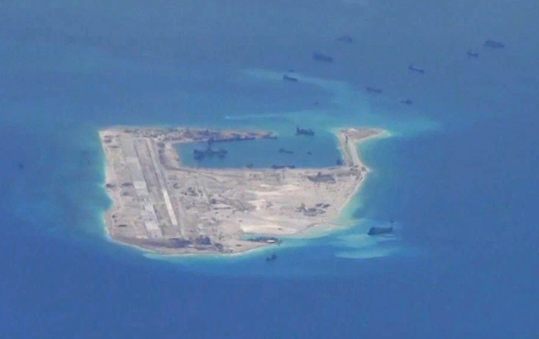 FILE - Chinese dredging vessels are purportedly seen in the waters around Fiery Cross Reef in the disputed Spratly Islands in the South China Sea in this still image from video taken by a P-8A Poseidon surveillance aircraft provided by the United Sta...